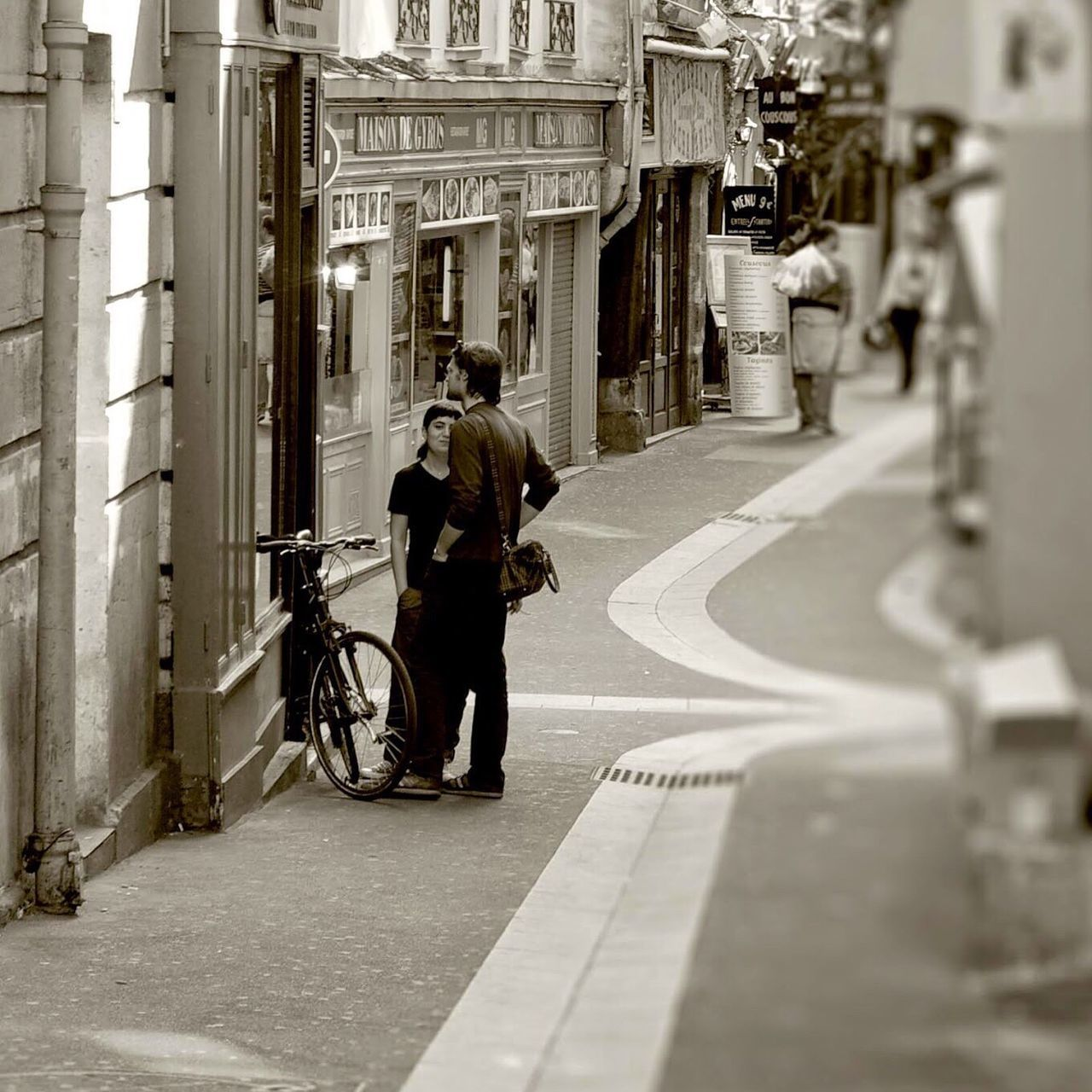 bicycle, real people, architecture, transportation, walking, built structure, men, land vehicle, mode of transport, building exterior, day, full length, lifestyles, road, outdoors, city, women, adult, people