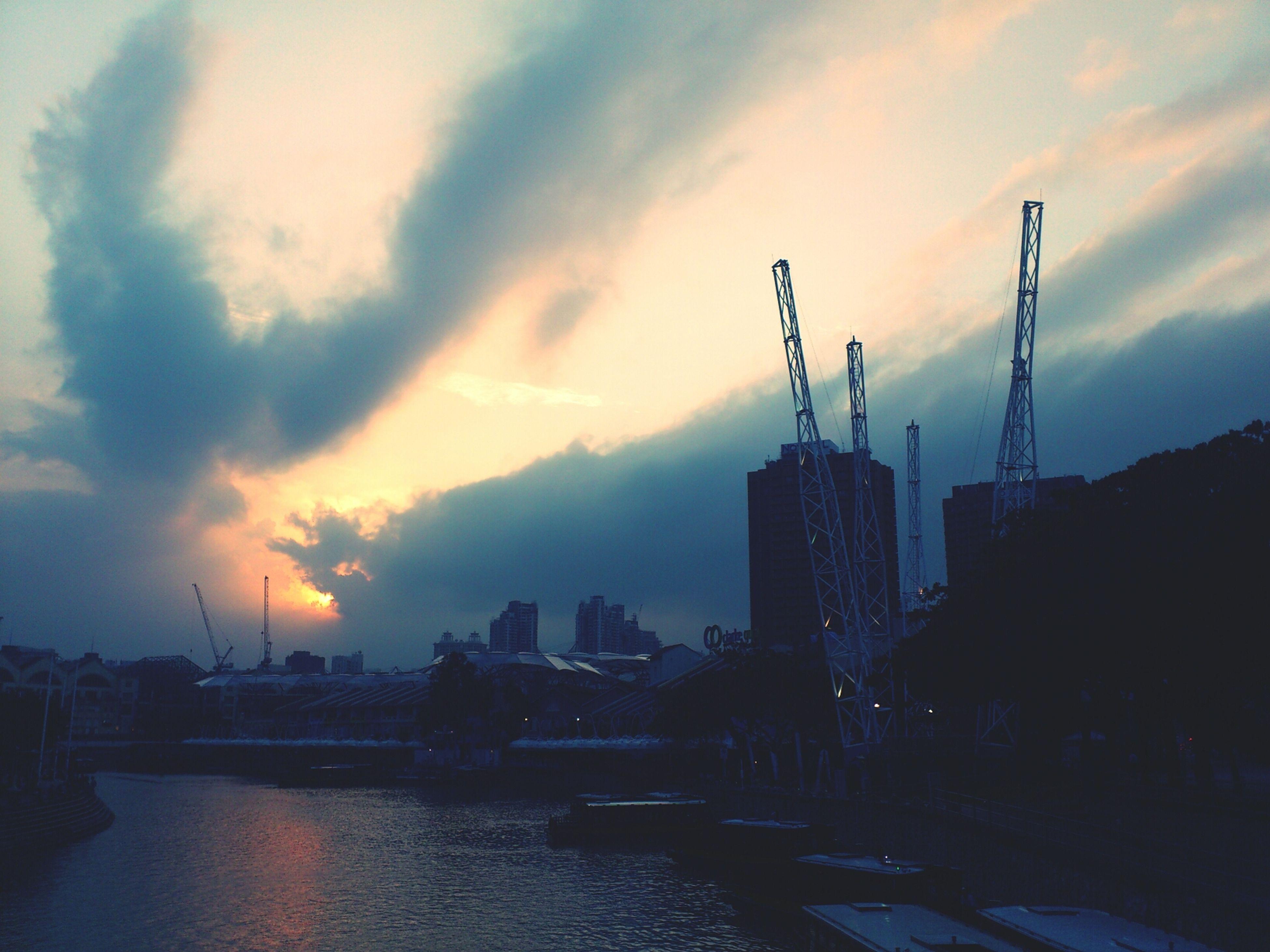 sunset, architecture, building exterior, built structure, sky, cloud - sky, city, water, crane - construction machinery, orange color, river, waterfront, cloudy, silhouette, cityscape, cloud, industry, development, outdoors, no people