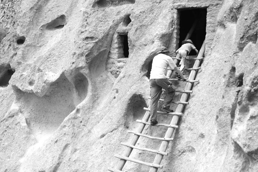A father and son explore some ruins at Bandelier National Monument.