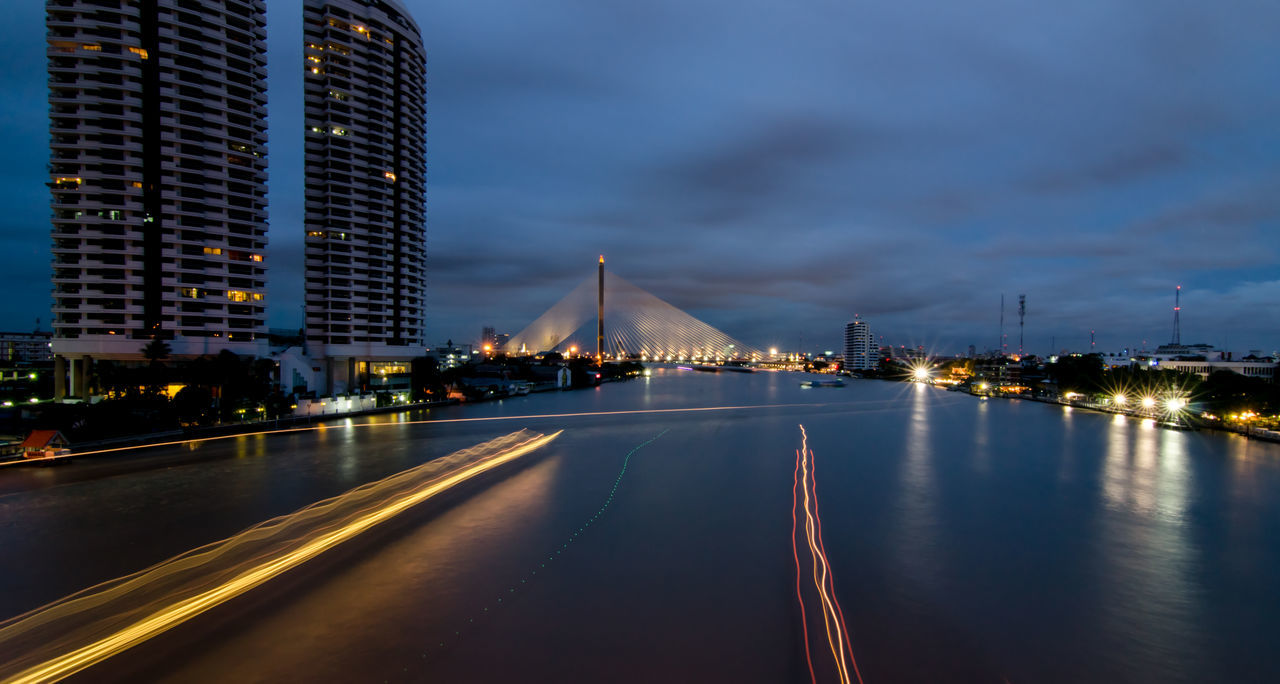 High Angle View Of Light Trails On River In City At Dusk
