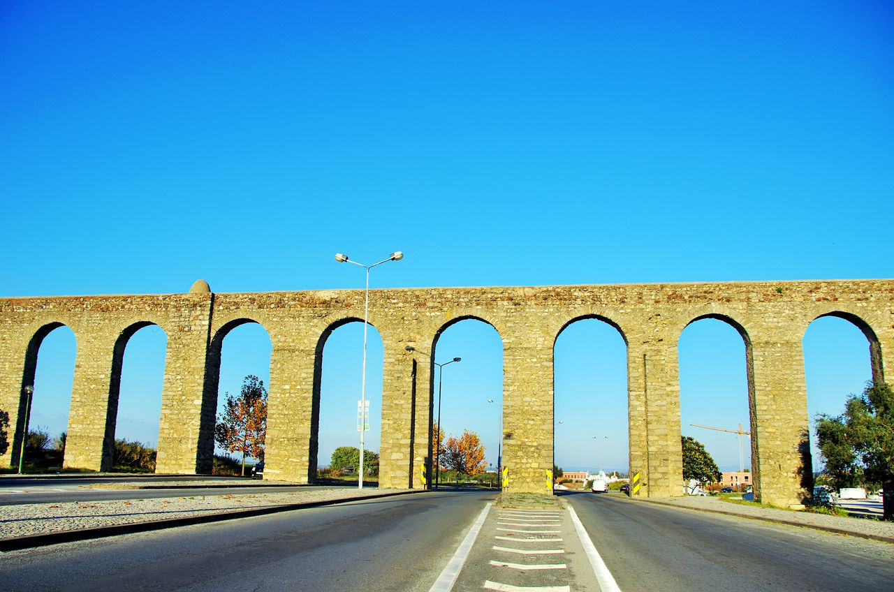 the way forward, copy space, arch, clear sky, transportation, road, day, built structure, bird, architecture, animal themes, outdoors, bridge - man made structure, animals in the wild, blue, nature, no people, sky