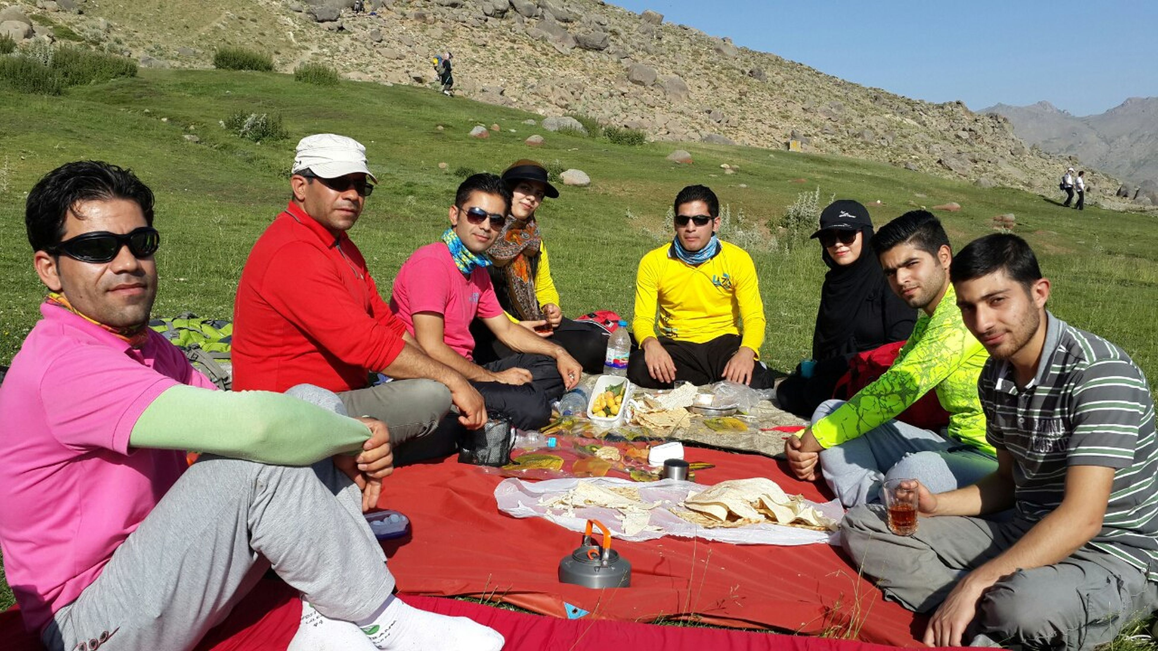 togetherness, leisure activity, lifestyles, sitting, friendship, mixed age range, standing, medium group of people, full length, casual clothing, front view, person, vacations, tourist, tourism, nature, enjoyment, day, tranquility, looking, outdoors, scenics, mountain