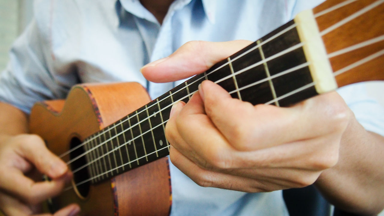 Man playing solo classical ukulele Bending Classic Close-up Day Fingers Folk Fretboard Guitar Hobbies Human Hand Indoors  Joy Melody Music Musical Instrument One Person Performance Playing Relaxing Song Strings Ukulele Wood