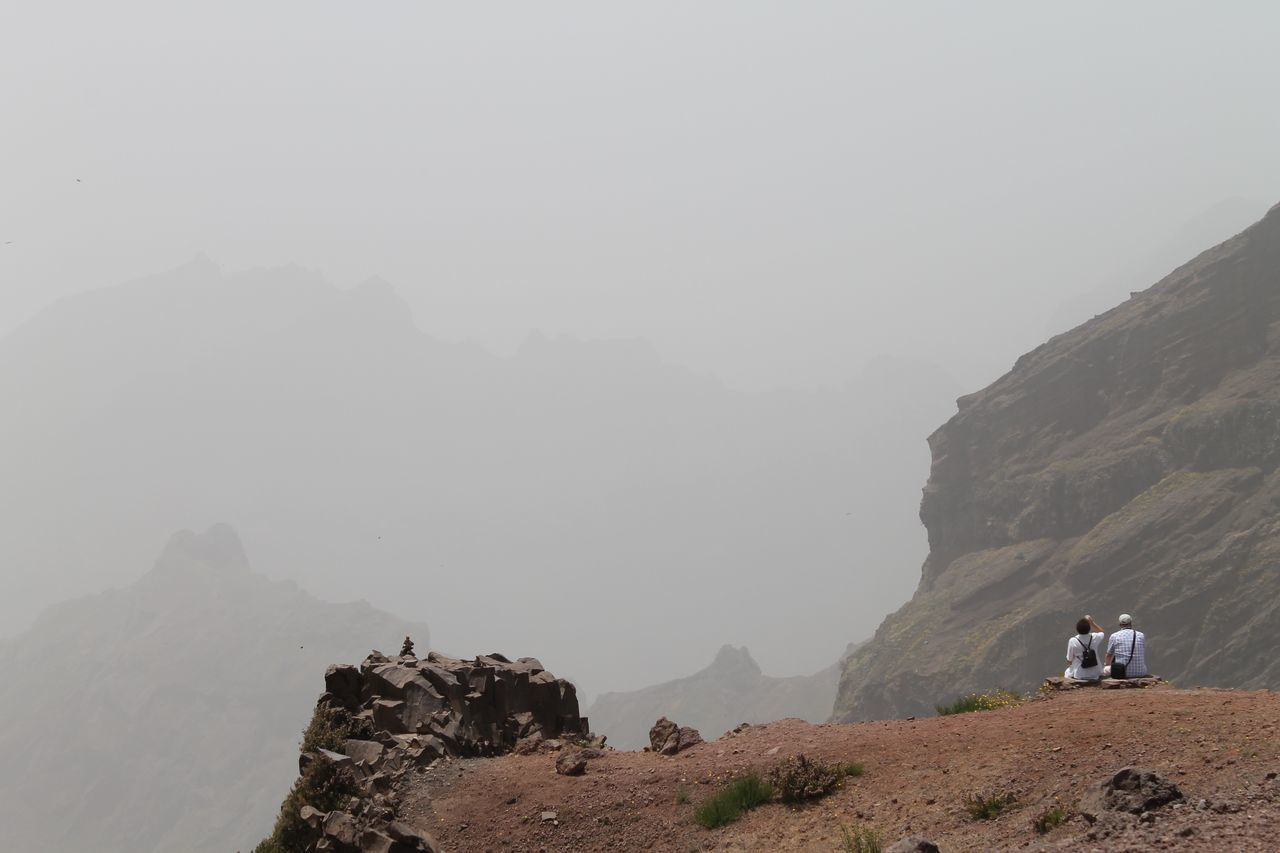 Rear View Of People Sitting On Cliff By Mountains Against Sky During Foggy Weather