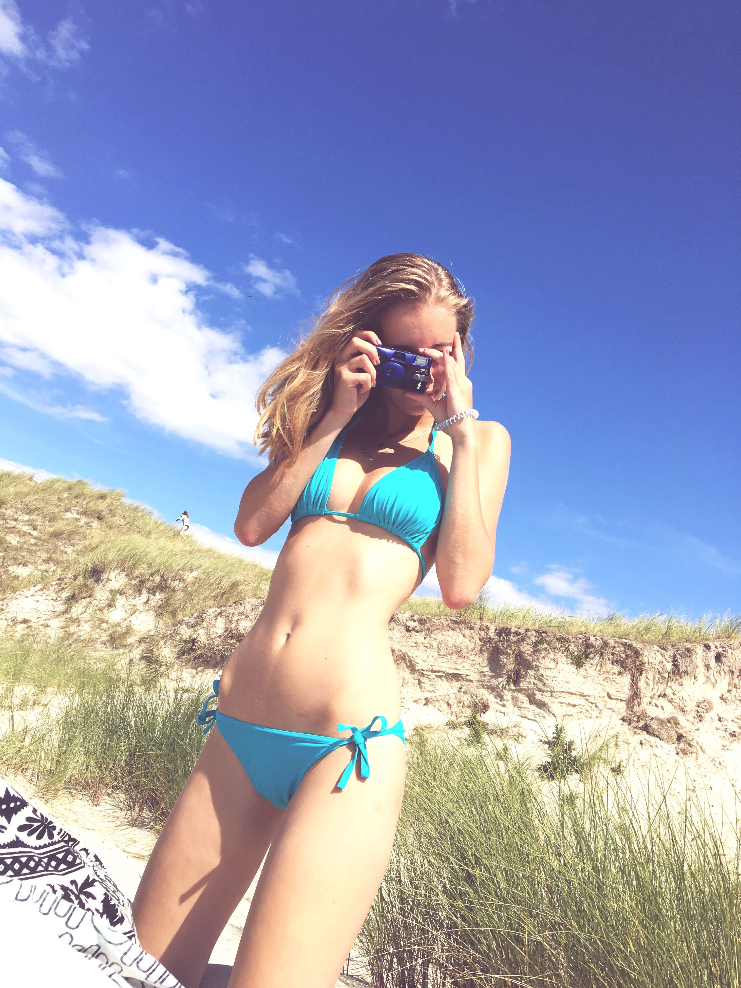 young women, young adult, sky, low angle view, person, leisure activity, lifestyles, sensuality, blue, summer, bikini, sunlight, sunny, femininity, relaxation, beauty, sunbathing, casual clothing, day, seductive woman, long hair, outdoors, nature, carefree