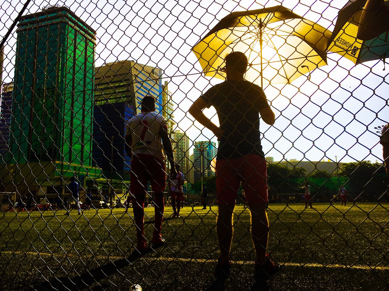 chainlink fence, sport, teamwork, real people, soccer, standing, sports team, men, competition, rear view, full length, togetherness, lifestyles, playing, activity, only men, playing field, goalie, leisure activity, competitive sport, soccer player, sportsman, team sport, match - sport, soccer field, adult, sports clothing, day, people, sky, outdoors, grass, goal post, adults only