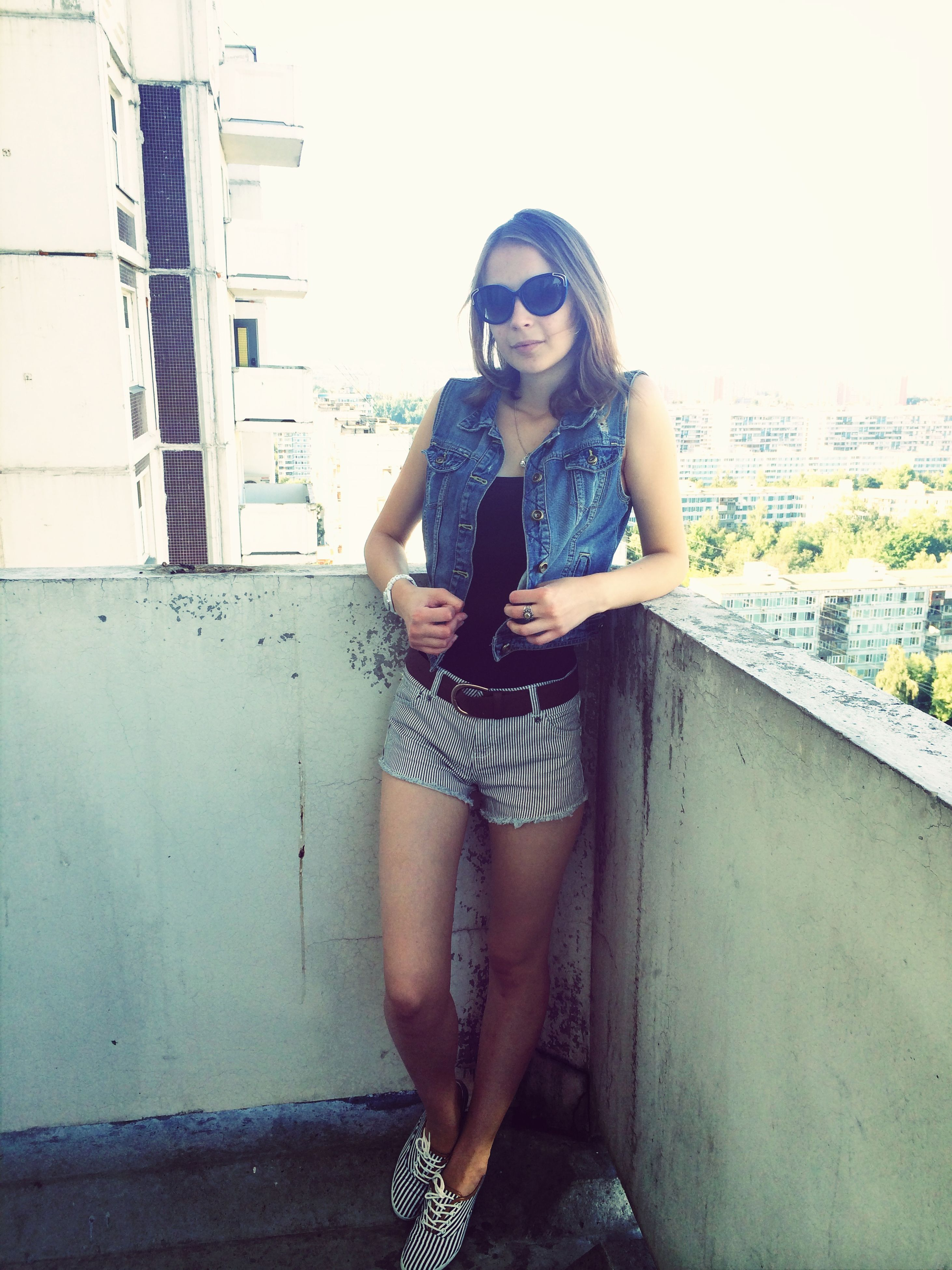 young adult, lifestyles, young women, casual clothing, leisure activity, person, full length, sunglasses, standing, built structure, architecture, building exterior, sitting, portrait, front view, three quarter length, looking at camera