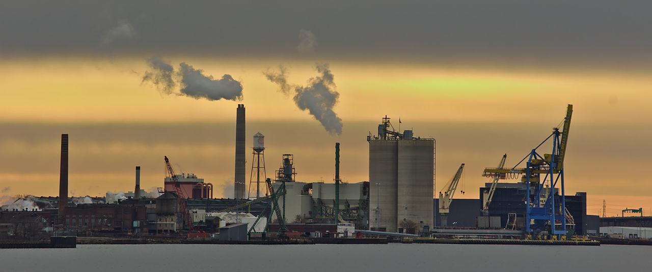 Industrial riverfront landscape with pollution and water. Business Business Finance And Industry Environment Factory Fuel And Power Generation Gas Industry No People Oil Industry Outdoors Petrochemical Plant Refinery Smoke Stack Sunset Technology