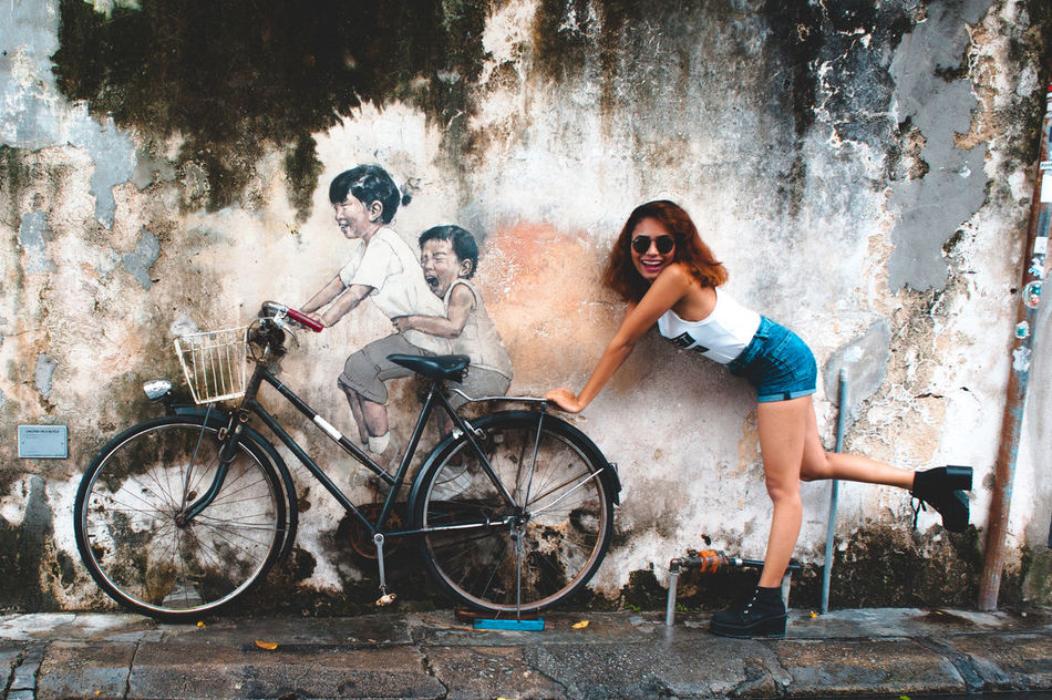 Adult Art Is Everywhere Beautiful People Bicycle Cheerful City Couple - Relationship Day Enjoyment Friendship Full Length Fun Happiness Looking At Camera Outdoors Portrait Smiling Standing Togetherness Two People Women Young Adult Young Men Young Women Youth Culture