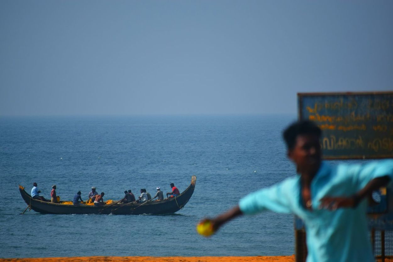 These men were kids once.. Sea Blue Water Standing Horizon Over Water Skill  Sky Men People Real People Outdoors Occupation Working Only Men Spread Wings Kerala Gods Own Country Freshness Shankumugham Teamwork Beach Beachphotography Playing Cricket! Fishing Boat