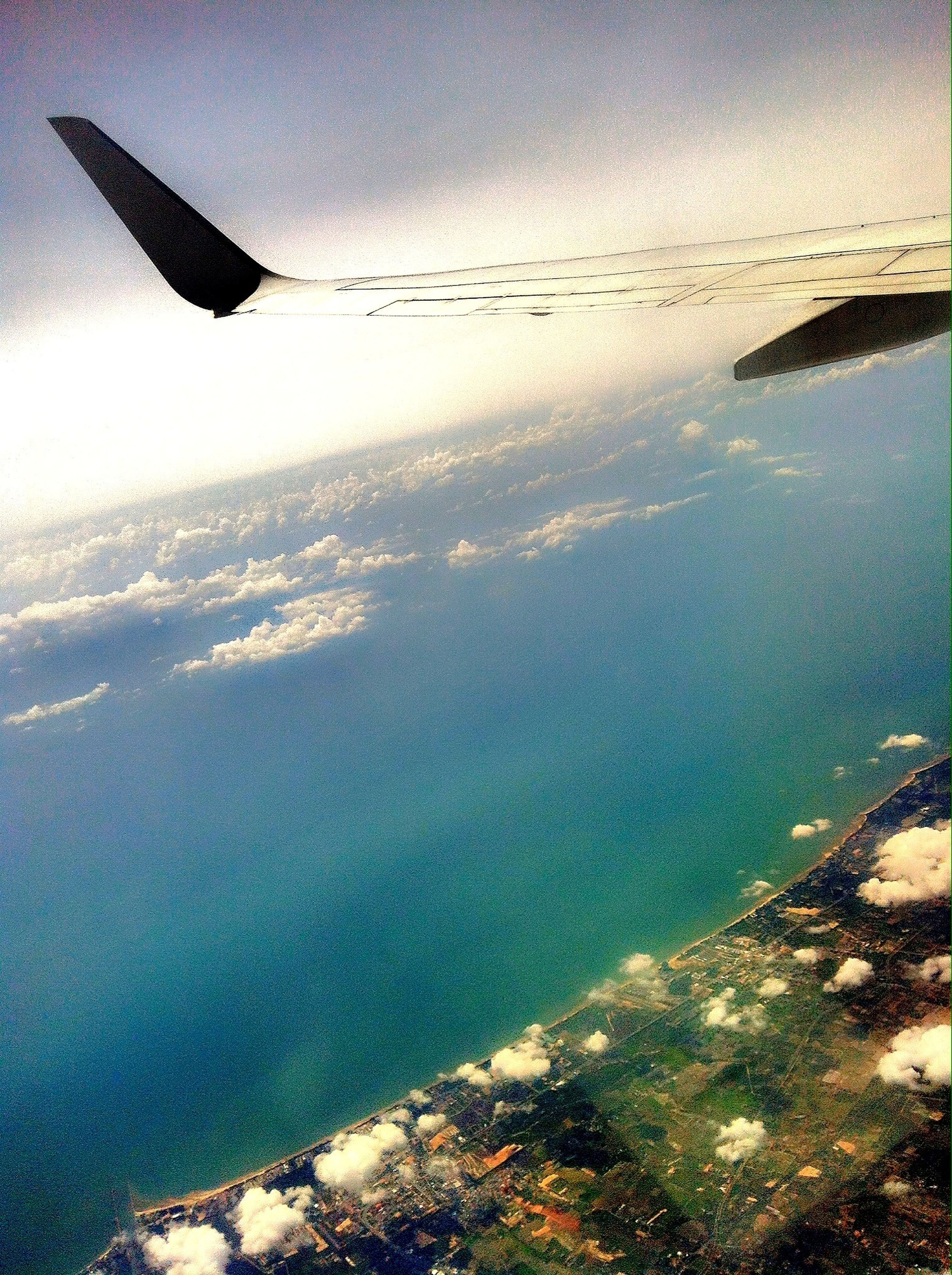 sea, water, aerial view, aircraft wing, scenics, flying, transportation, airplane, mode of transport, tranquil scene, air vehicle, beauty in nature, part of, nature, tranquility, sky, horizon over water, cropped, travel, mid-air