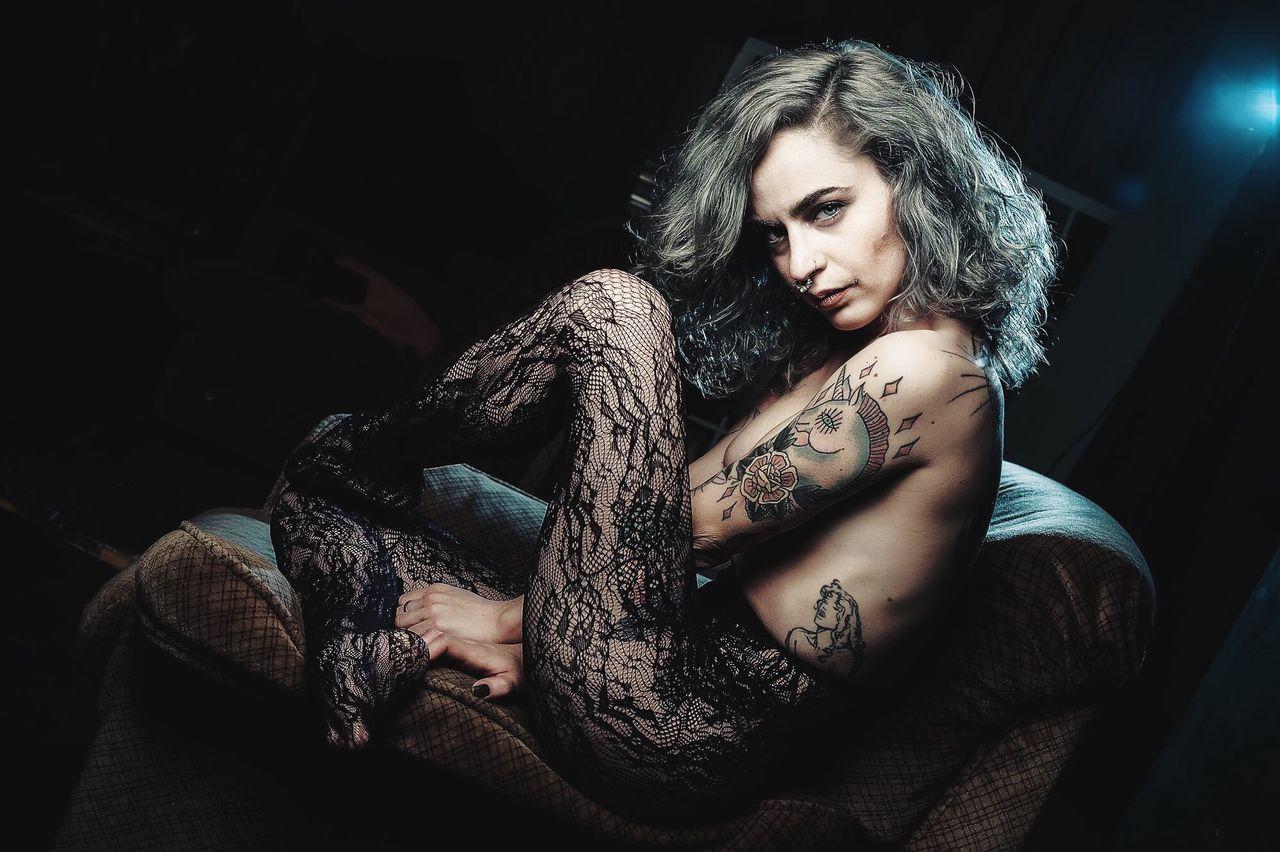 one person, sitting, young adult, young women, tattoo, leisure activity, real people, beautiful woman, looking at camera, indoors, full length, blond hair, portrait, one young woman only, day, adult, people
