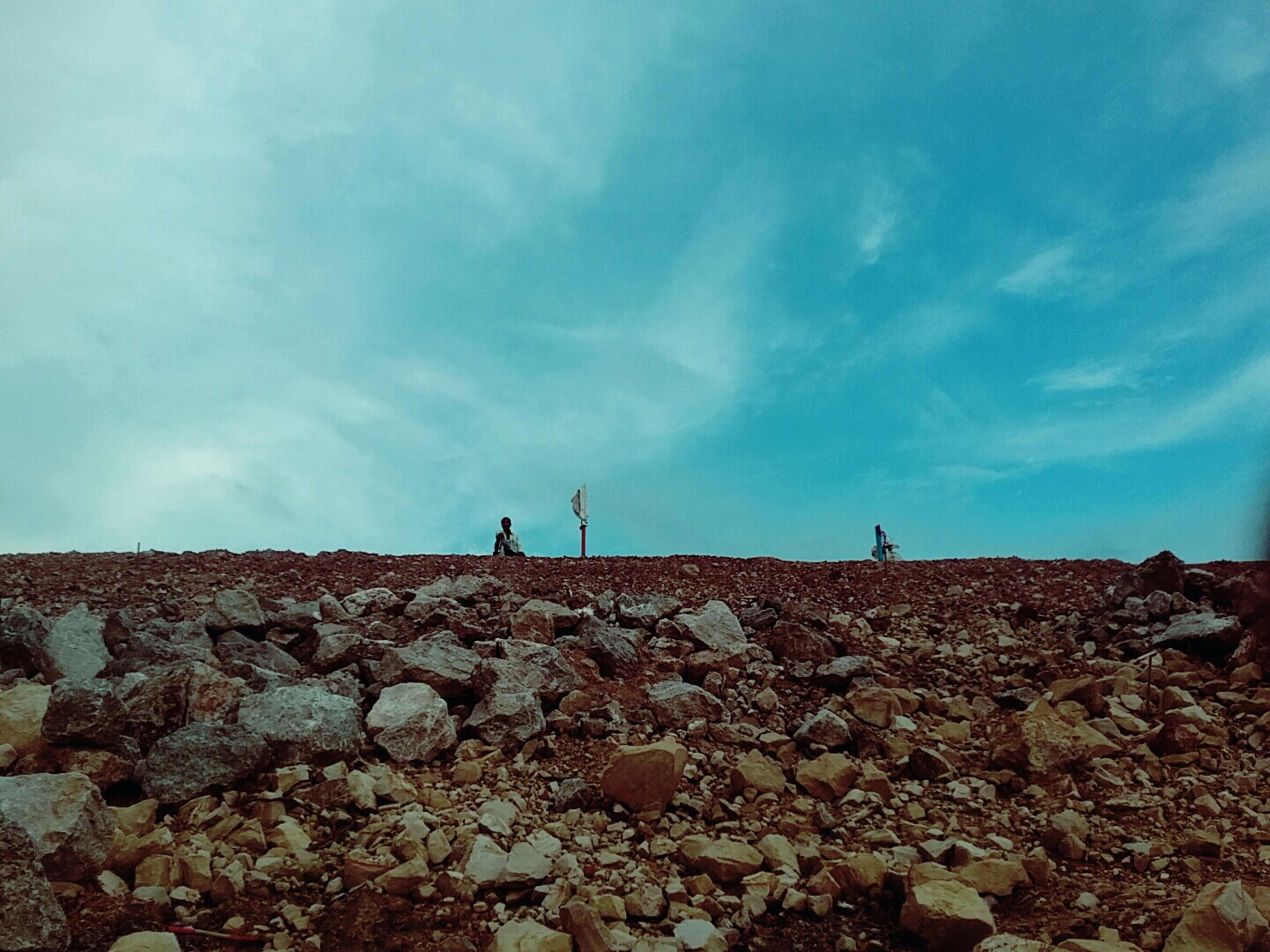 sky, leisure activity, lifestyles, men, rock - object, low angle view, blue, nature, full length, tranquility, cloud - sky, beauty in nature, tranquil scene, scenics, unrecognizable person, day, rock