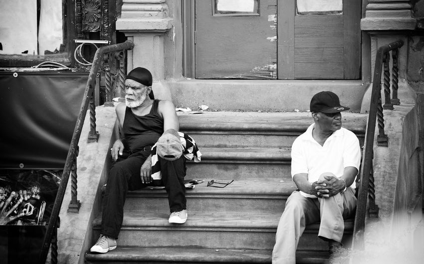 Two people sitting on the steps of an entrance of a house in Harlem district Angry Architecture Black And White Friday Boys Building Exterior Childhood Criminality Criminals Day Full Length Harlem  Men Outdoors People Real People Sitting Two People