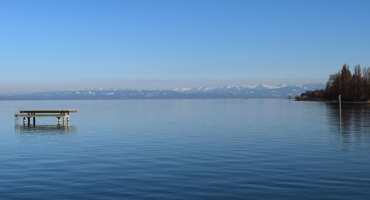 water, blue, clear sky, tranquility, scenics, sea, outdoors, tranquil scene, sky, nature, no people, mountain, day, beauty in nature, landscape, architecture, horizon over water