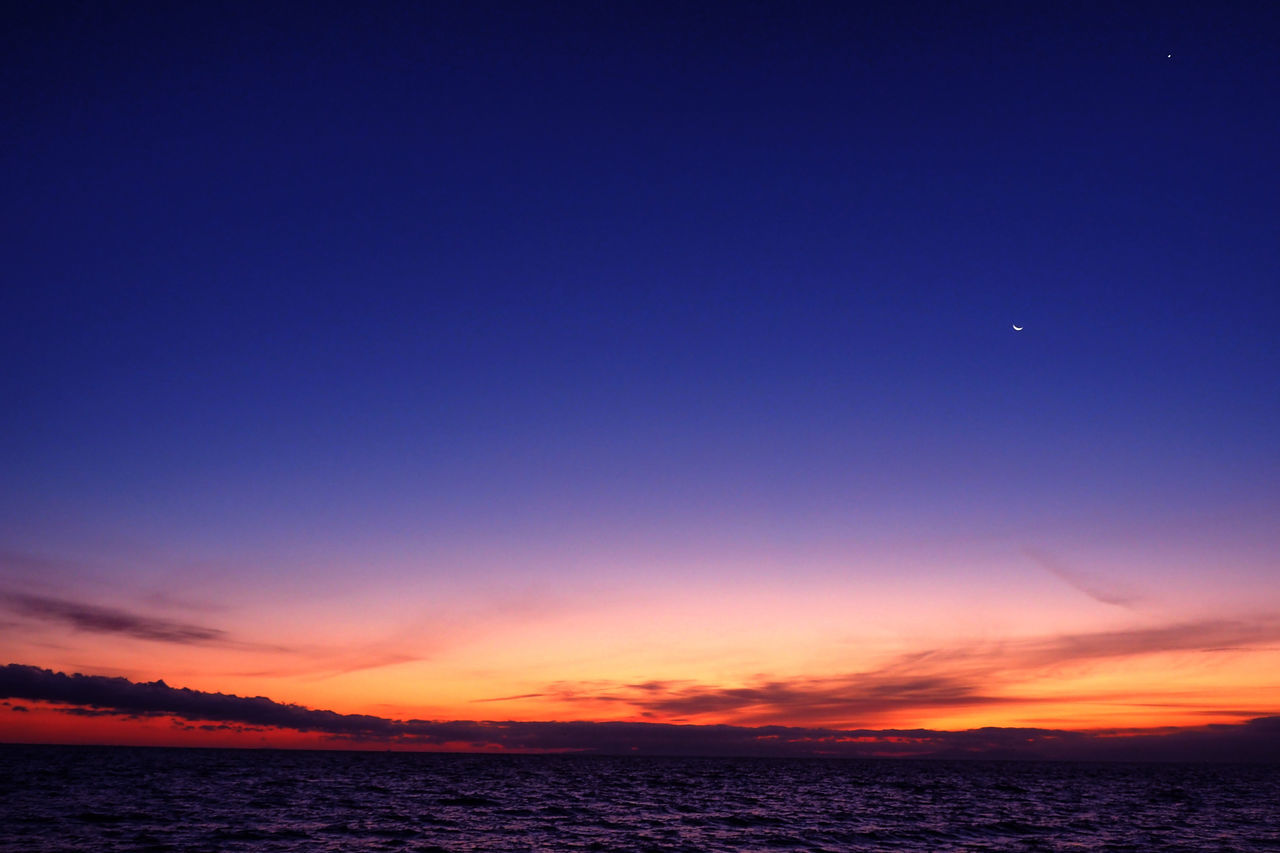 sunset, beauty in nature, copy space, scenics, nature, tranquil scene, moon, silhouette, sea, sky, tranquility, water, blue, dusk, clear sky, outdoors, no people, horizon over water, crescent, astronomy