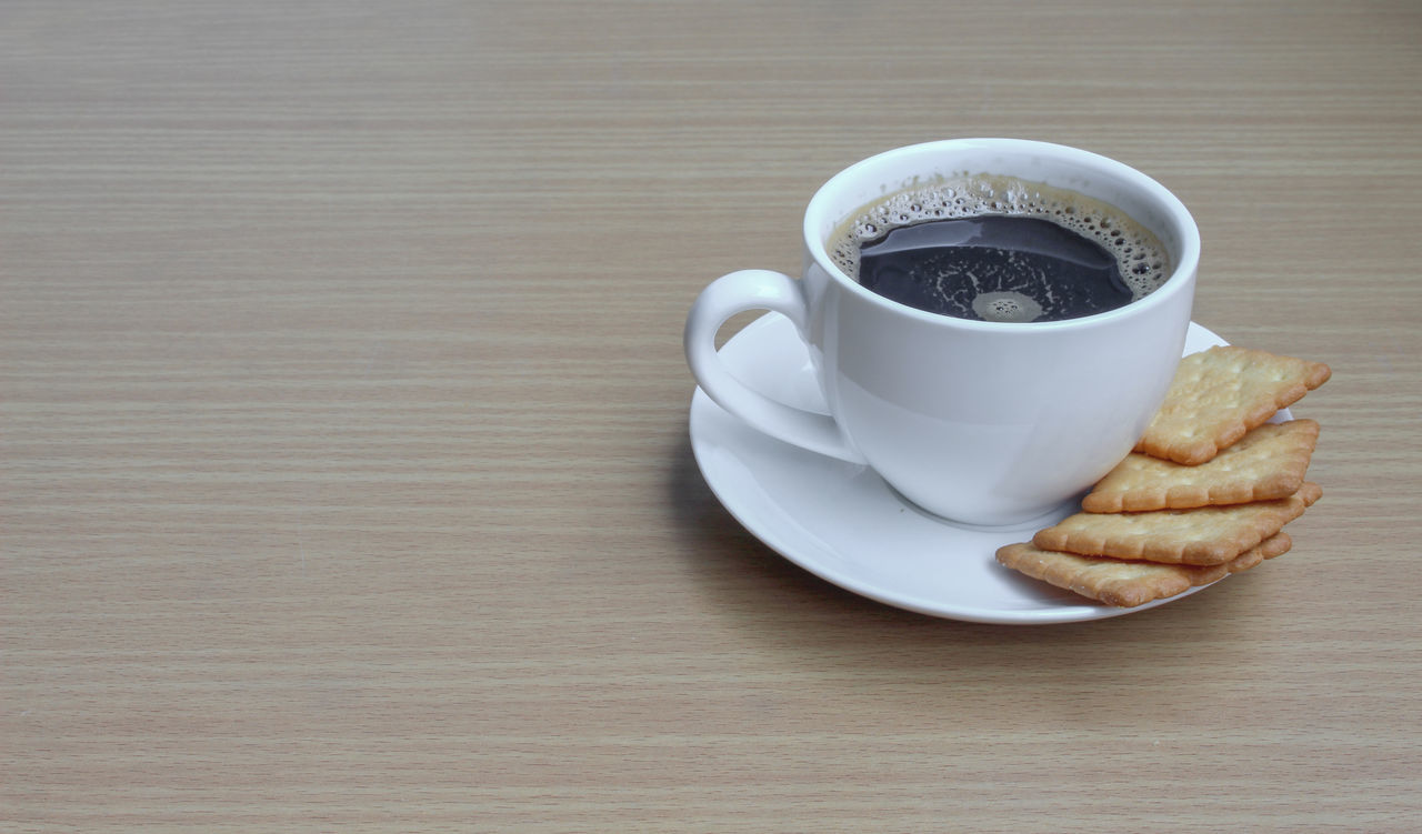 Close-Up Of Coffee Cup And Biscuits On Table
