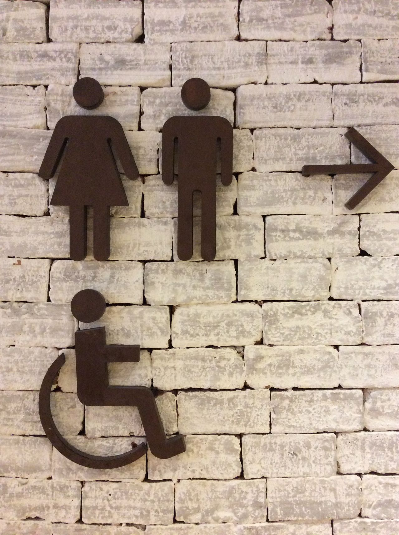 Bangkok Thailand. Signage Men Women Disabled Arrow pointing right Restroom Signage Interior Brick Wall White