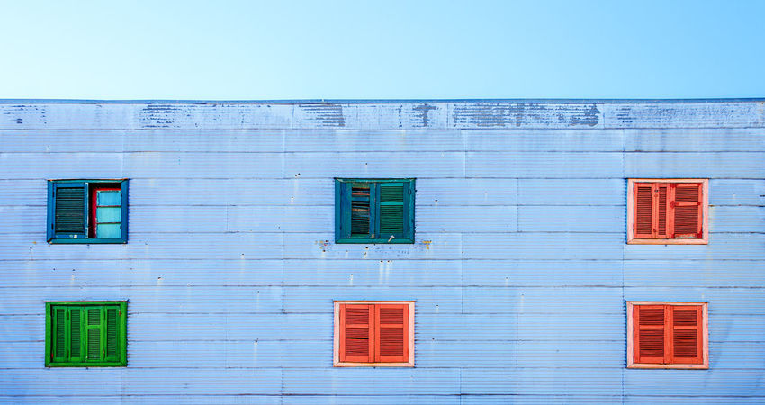Light blue wall with a blue sky and colorful windows in La Boca neighborhood in Buenos Aires, Argentina Architecture Argentina Blue Boca Buenos Aires Caminito Colorful Corrugated Green La Boca La Boca, Buenos Aires Landmark Latin Latino Neighborhood Pink South America Tango Walls Window Windows