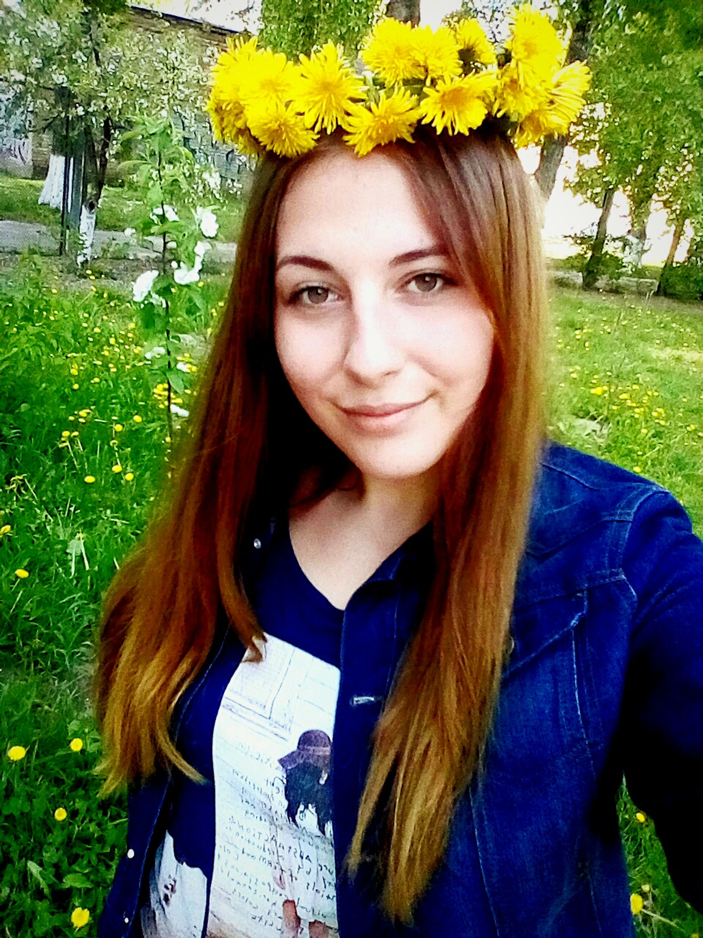 looking at camera, portrait, front view, flower, real people, young women, young adult, smiling, one person, day, beautiful woman, outdoors, long hair, lawn, grass, casual clothing, nature, leisure activity, lifestyles, happiness, park - man made space, standing, close-up