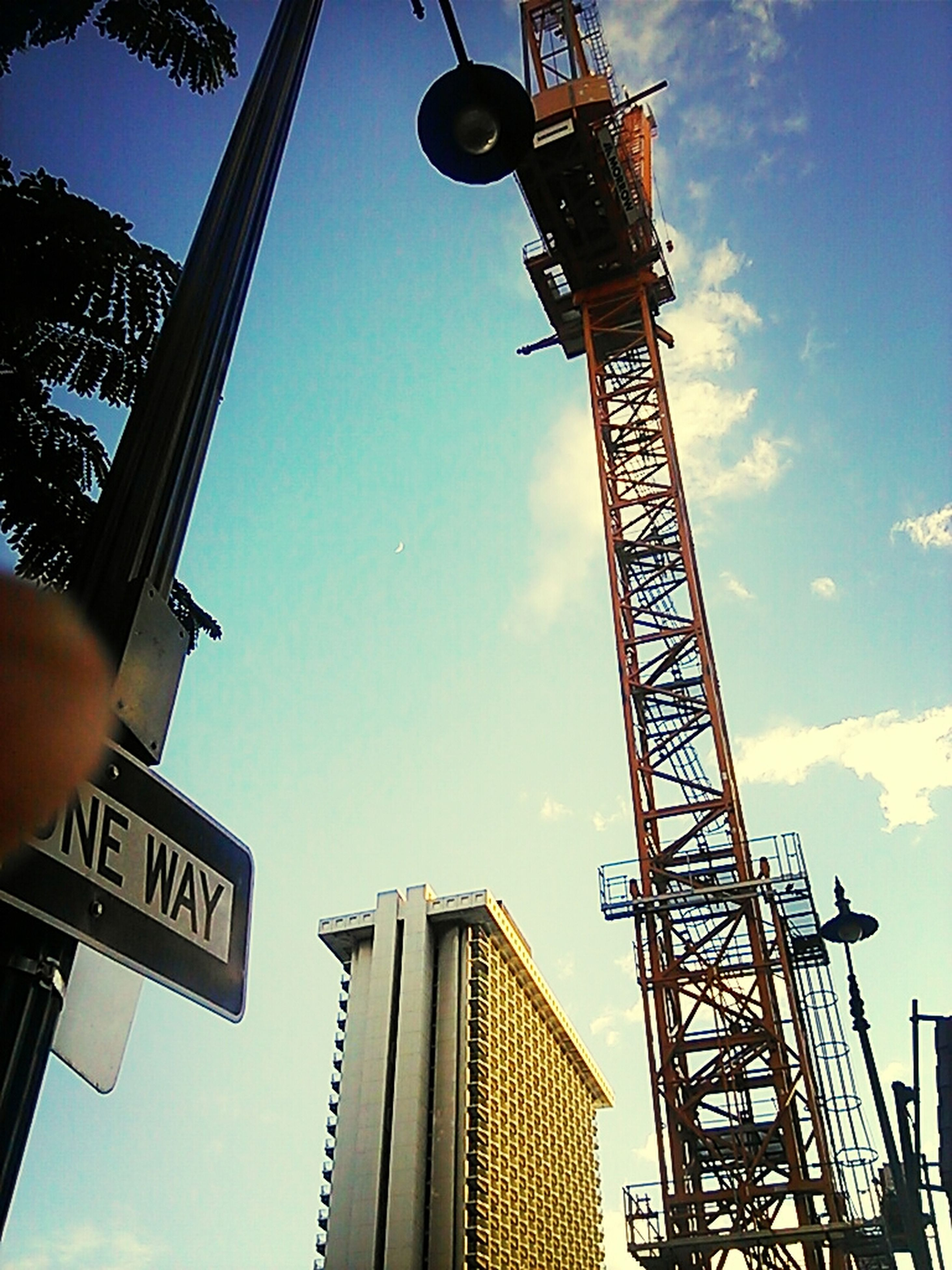 low angle view, architecture, built structure, tower, tall - high, sky, building exterior, communication, communications tower, street light, blue, lighting equipment, tall, outdoors, dusk, no people, city, crane - construction machinery, metal, silhouette