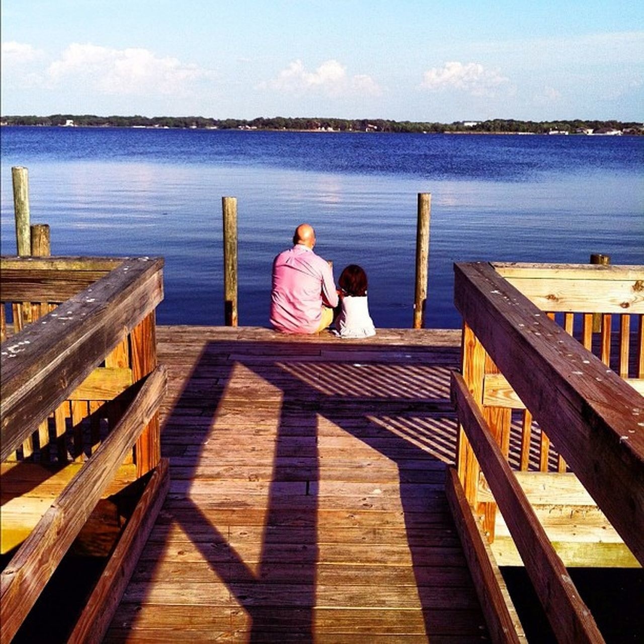 two people, water, pier, togetherness, leisure activity, wood - material, real people, jetty, day, men, nature, love, rear view, sea, sitting, scenics, wood paneling, outdoors, beauty in nature, sky, lifestyles, full length, bonding, women, fishing pole, people