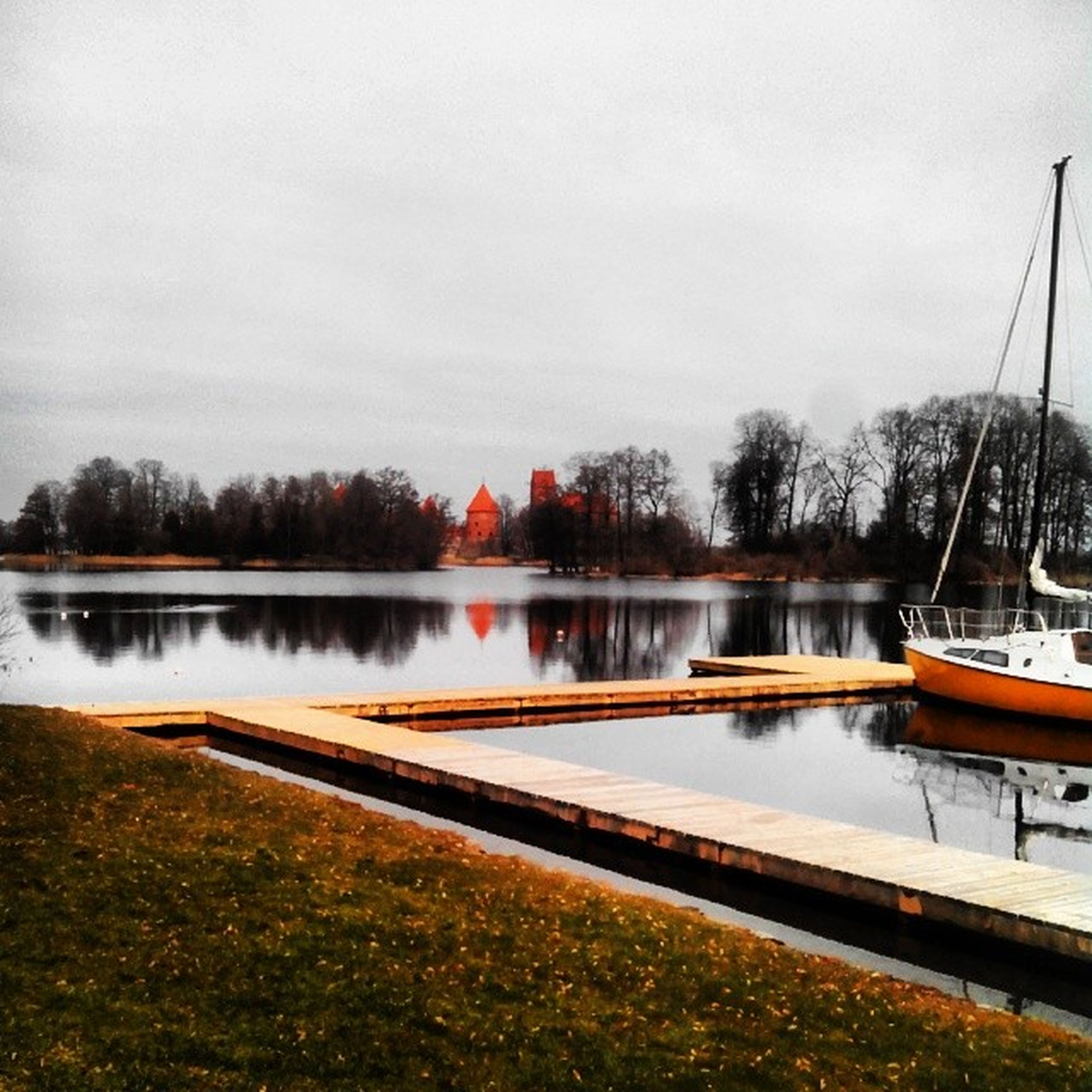 transportation, water, nautical vessel, moored, lake, boat, tree, mode of transport, reflection, sky, tranquility, tranquil scene, nature, scenics, pier, beauty in nature, river, outdoors, day, lakeshore