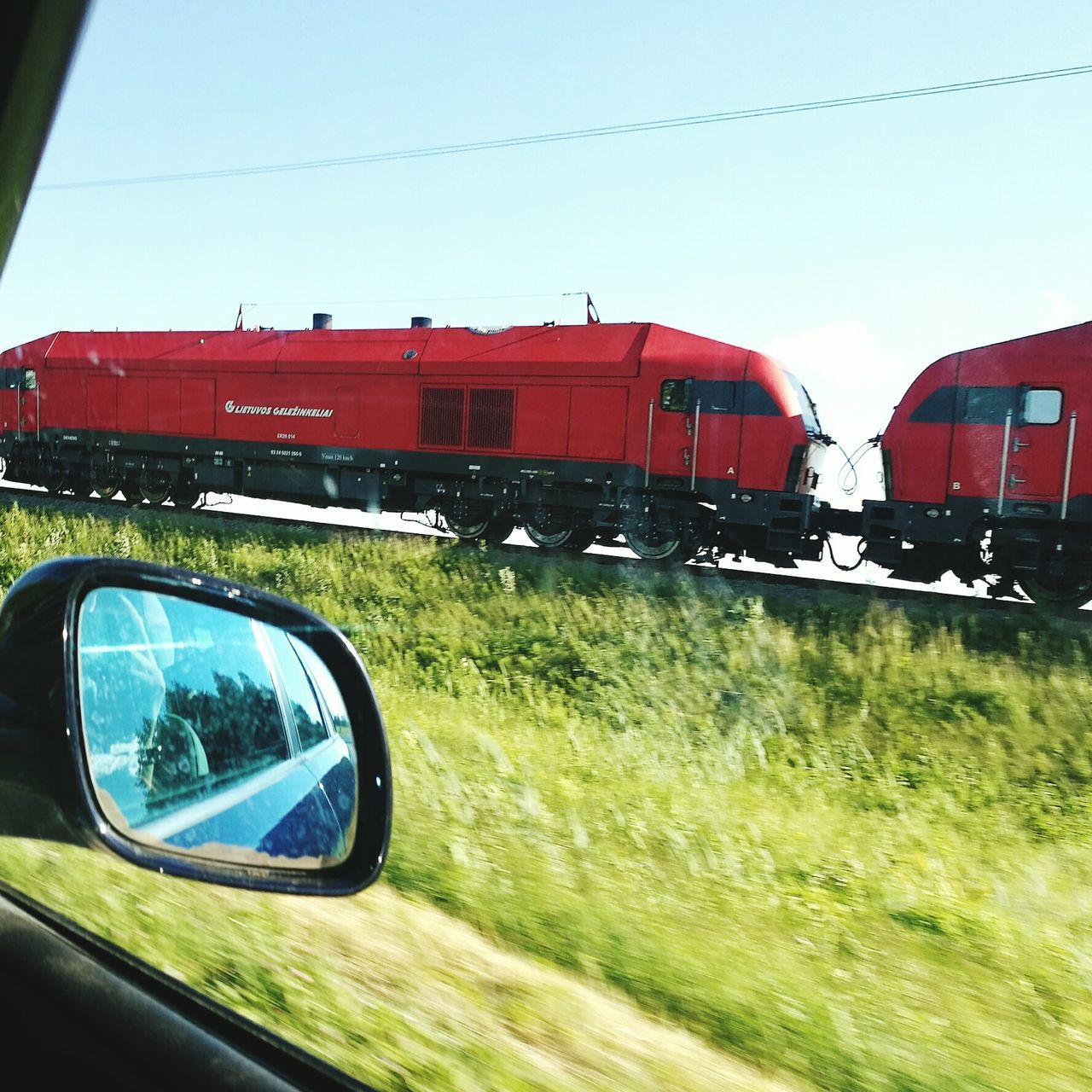 transportation, mode of transport, train - vehicle, rail transportation, grass, day, land vehicle, public transportation, no people, red, outdoors, railroad track, clear sky, nature, sky, locomotive