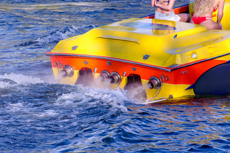 people relax on a hot summers day on a powerful race boat in lake Michigan USA Racing Boat Summertime Water Reflections Woman Adult Boats Day Fast Human Body Part Lake Leisure Activity Nature Nautical Vessel Outdoors People Speed Summer Water Waterfront Yellow