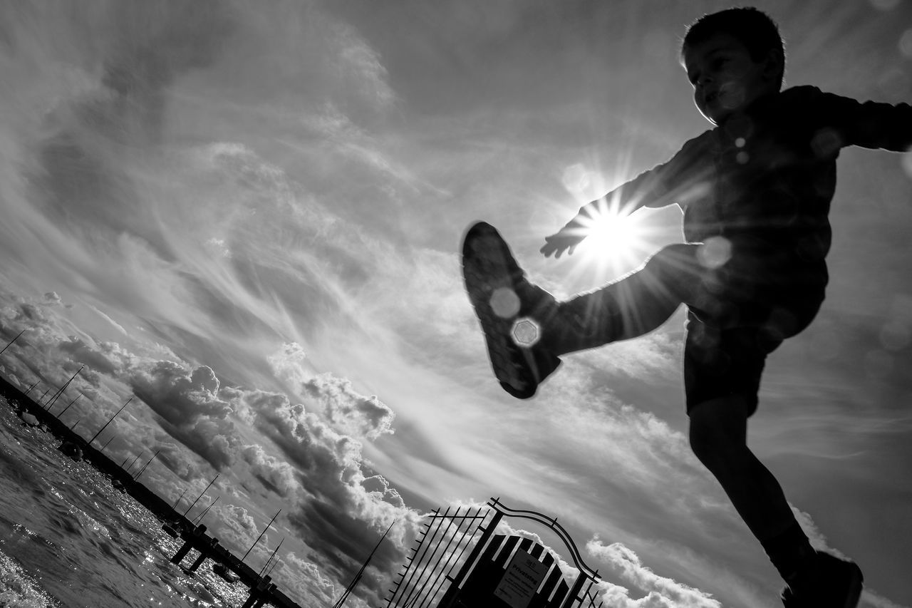 cloud - sky, sunbeam, low angle view, full length, sky, real people, mid-air, sunlight, one person, sun, leisure activity, outdoors, men, energetic, day, motion, jumping, water, nature, young adult, people