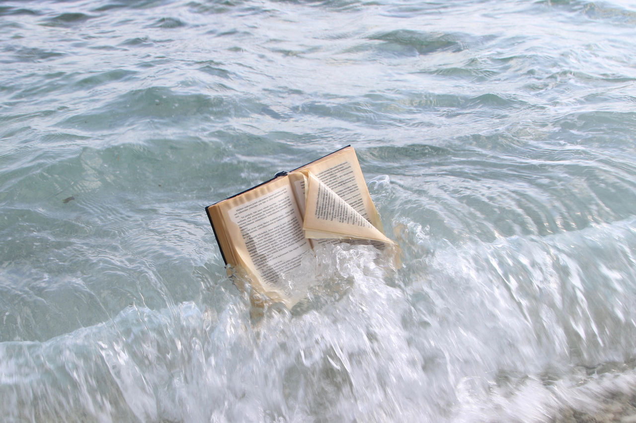 Book Day Floating On Water Flotsam High Angle View Message Without Bottle Motion Nature No People On Top Of The Wave Open Book  Outdoors Sea Swept Ashore Water