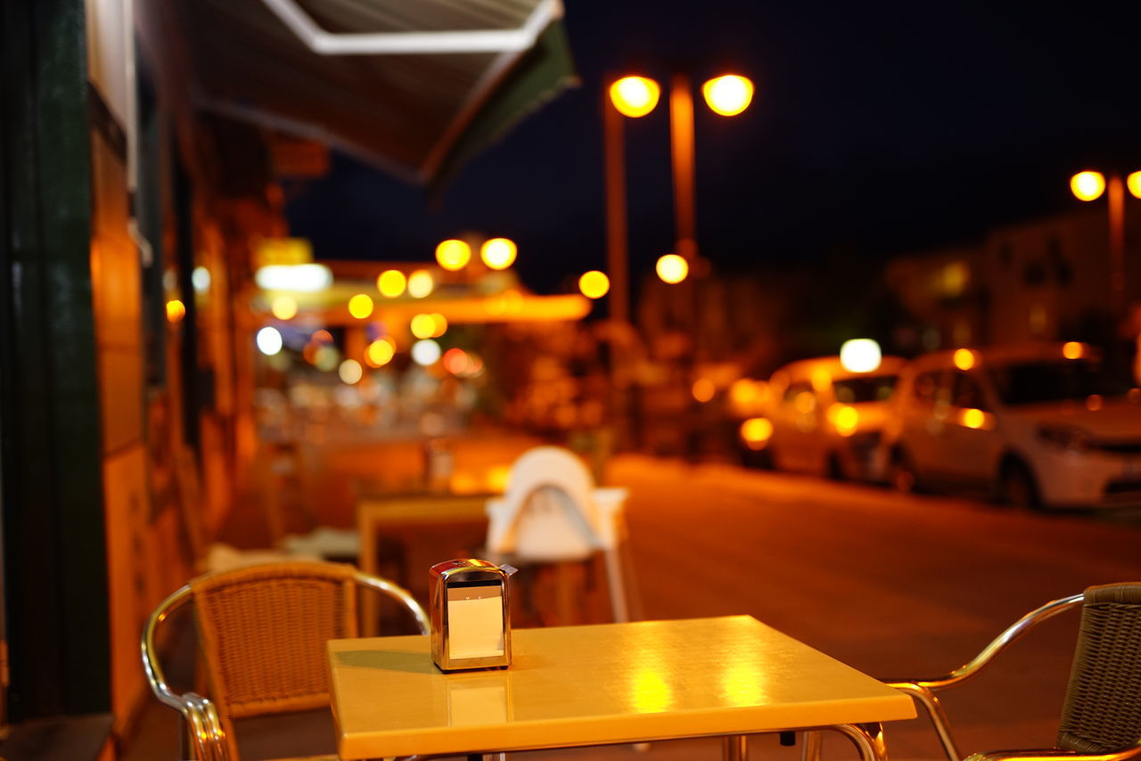 table, restaurant, night, illuminated, chair, cafe, focus on foreground, no people, food and drink, sidewalk cafe, place setting, drink, close-up, indoors, city, food