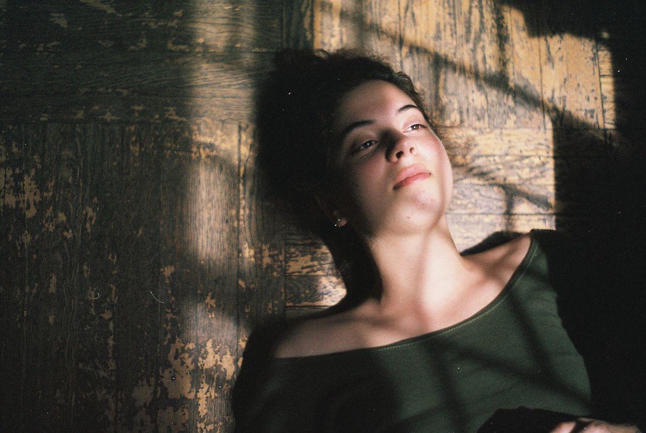 High Angle View Of Thoughtful Young Woman Lying On Hardwood Floor