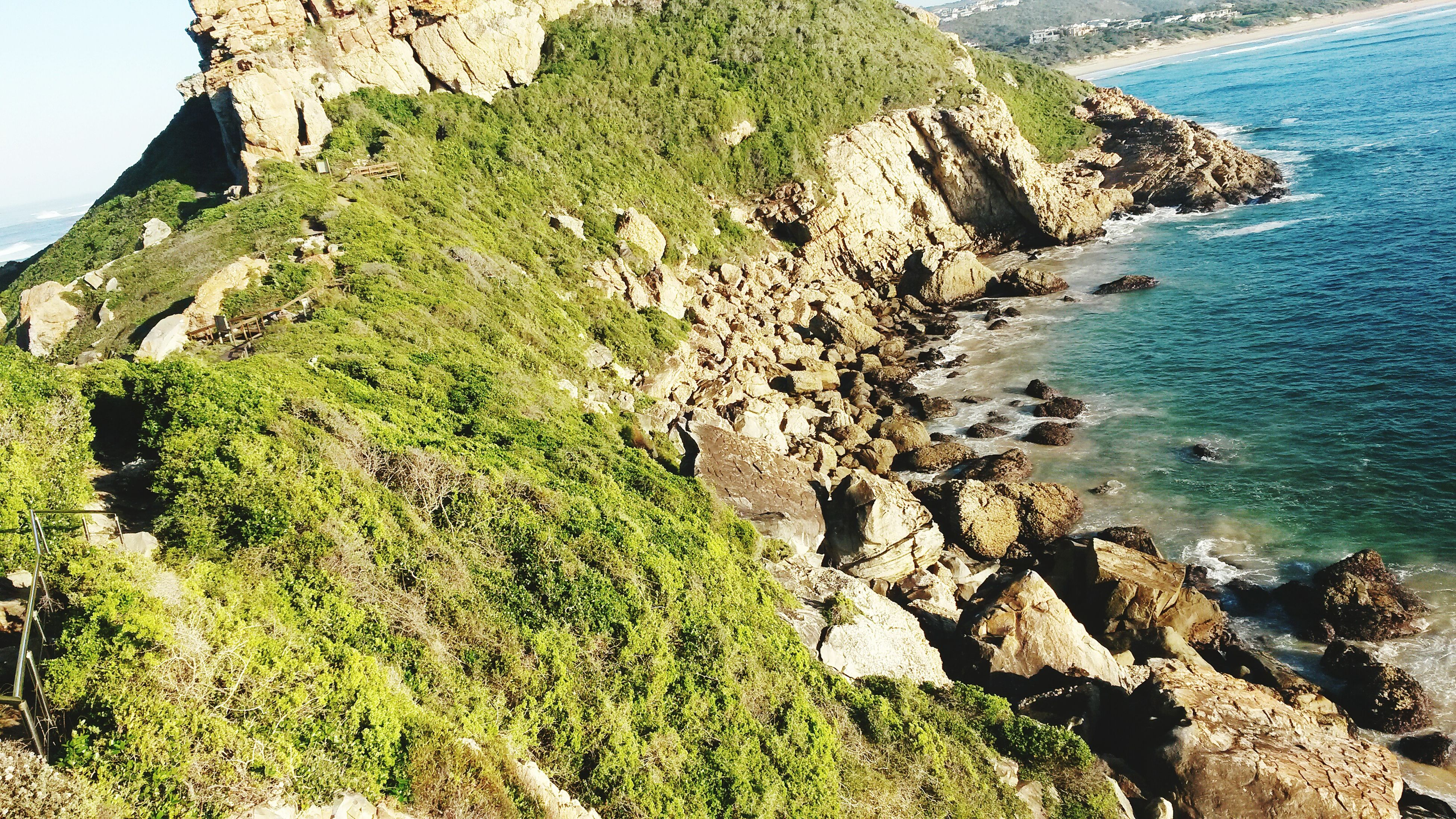 sea, water, tranquil scene, cliff, tranquility, rock formation, scenics, rock - object, horizon over water, beauty in nature, high angle view, nature, coastline, rock, plant, mountain, beach, idyllic, blue, day