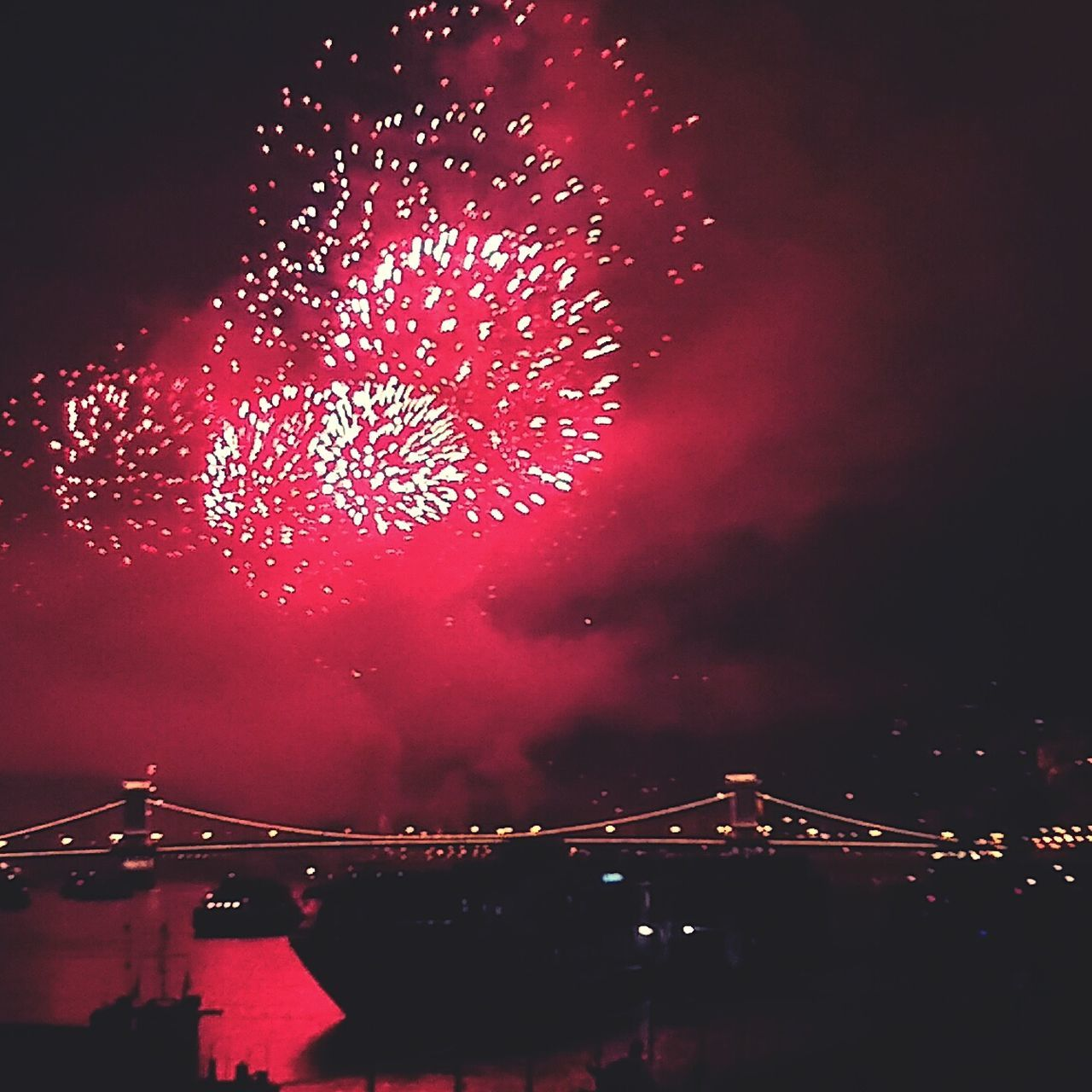 night, arts culture and entertainment, illuminated, firework display, celebration, firework - man made object, event, exploding, glowing, sky, outdoors, low angle view, red, long exposure, firework, no people, built structure