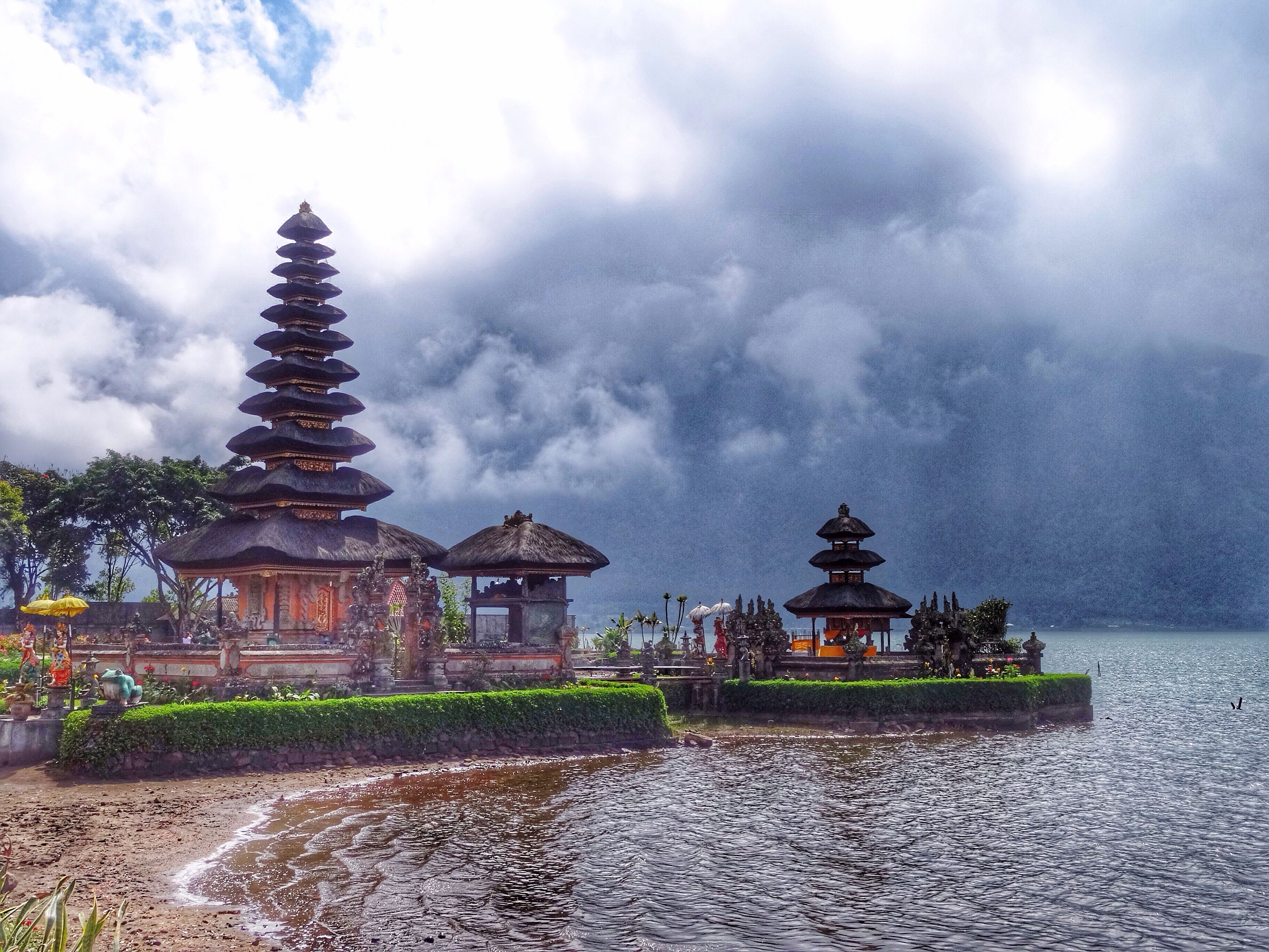 sky, water, built structure, architecture, cloud - sky, building exterior, fountain, religion, spirituality, place of worship, cloudy, temple - building, cloud, famous place, travel destinations, waterfront, sculpture, outdoors, spraying, nature