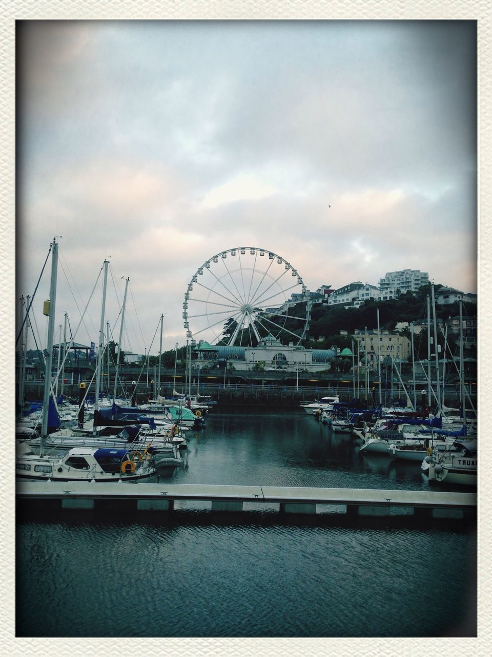 View Of Ferris Wheel In City Next To Sea Against Cloudy Sky