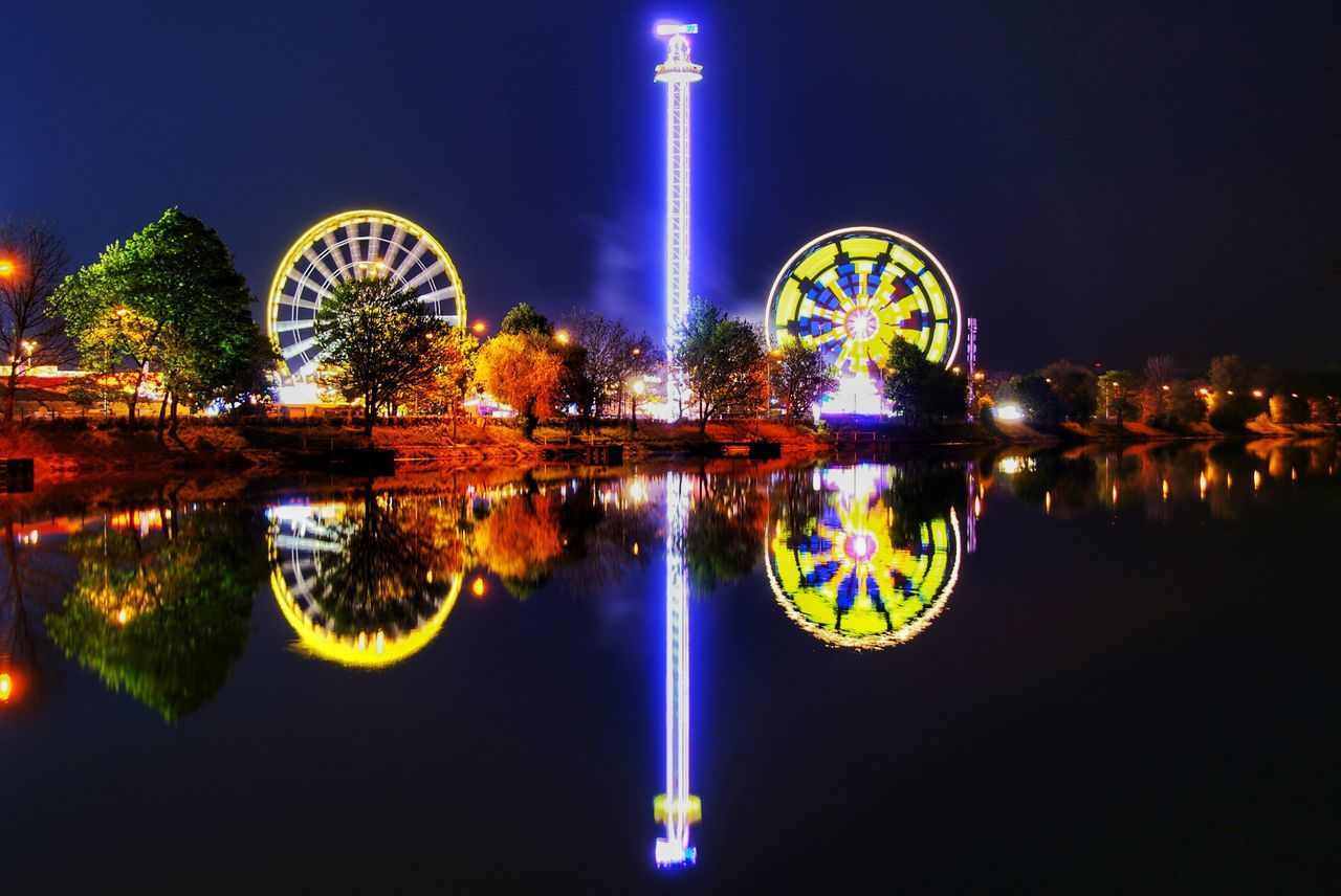 reflection, water, illuminated, night, multi colored, no people, waterfront, symmetry, ferris wheel, clear sky, reflecting pool, sky, outdoors, architecture, building exterior, nature
