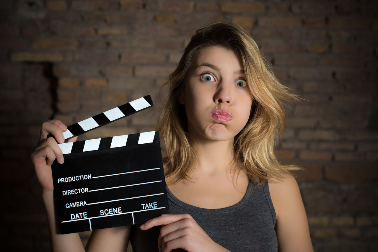 Portrait Of Young Woman Making Face While Holding Film Slate Against Brick Wall