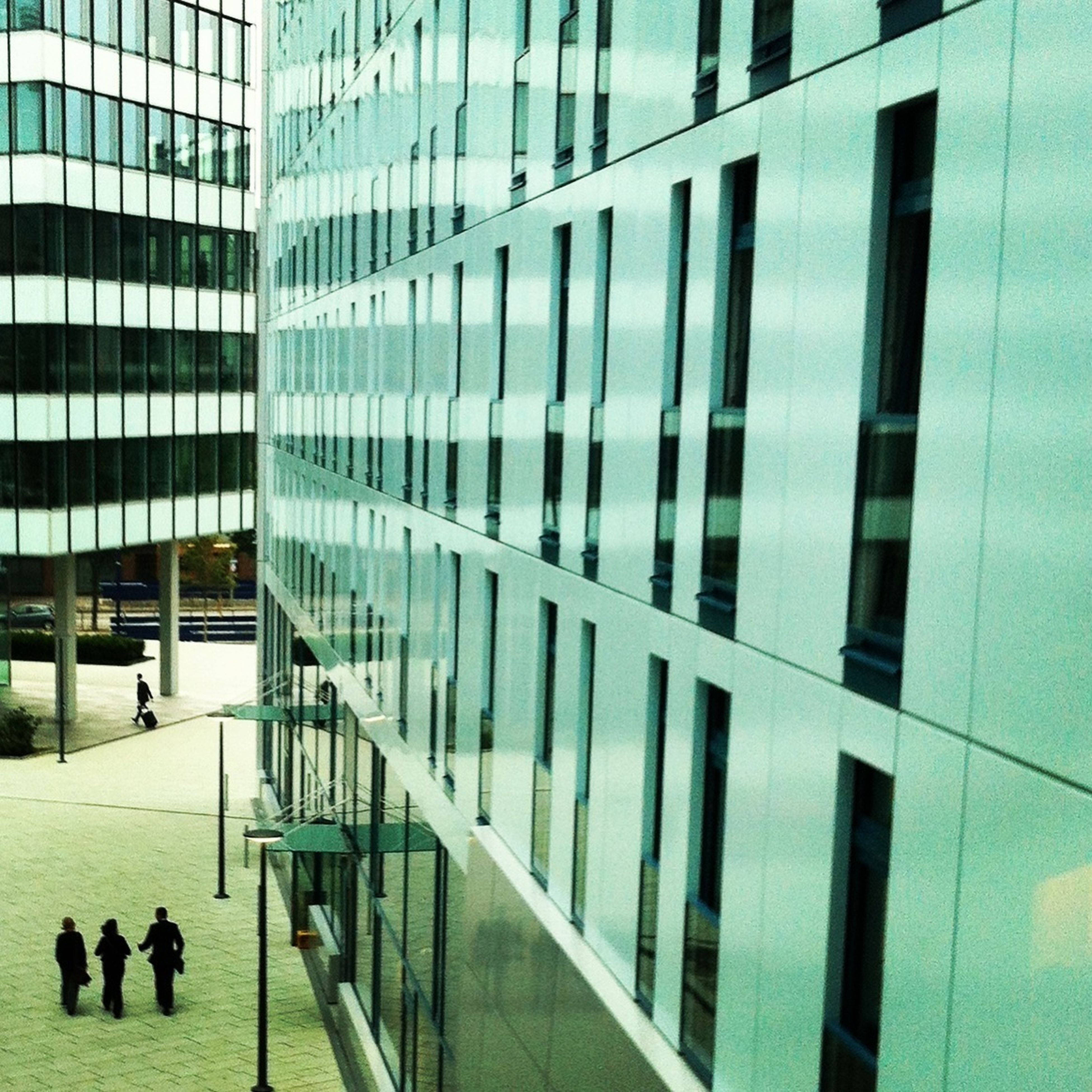 architecture, building exterior, built structure, city, modern, men, office building, building, walking, city life, glass - material, lifestyles, person, skyscraper, reflection, leisure activity, window, day, large group of people