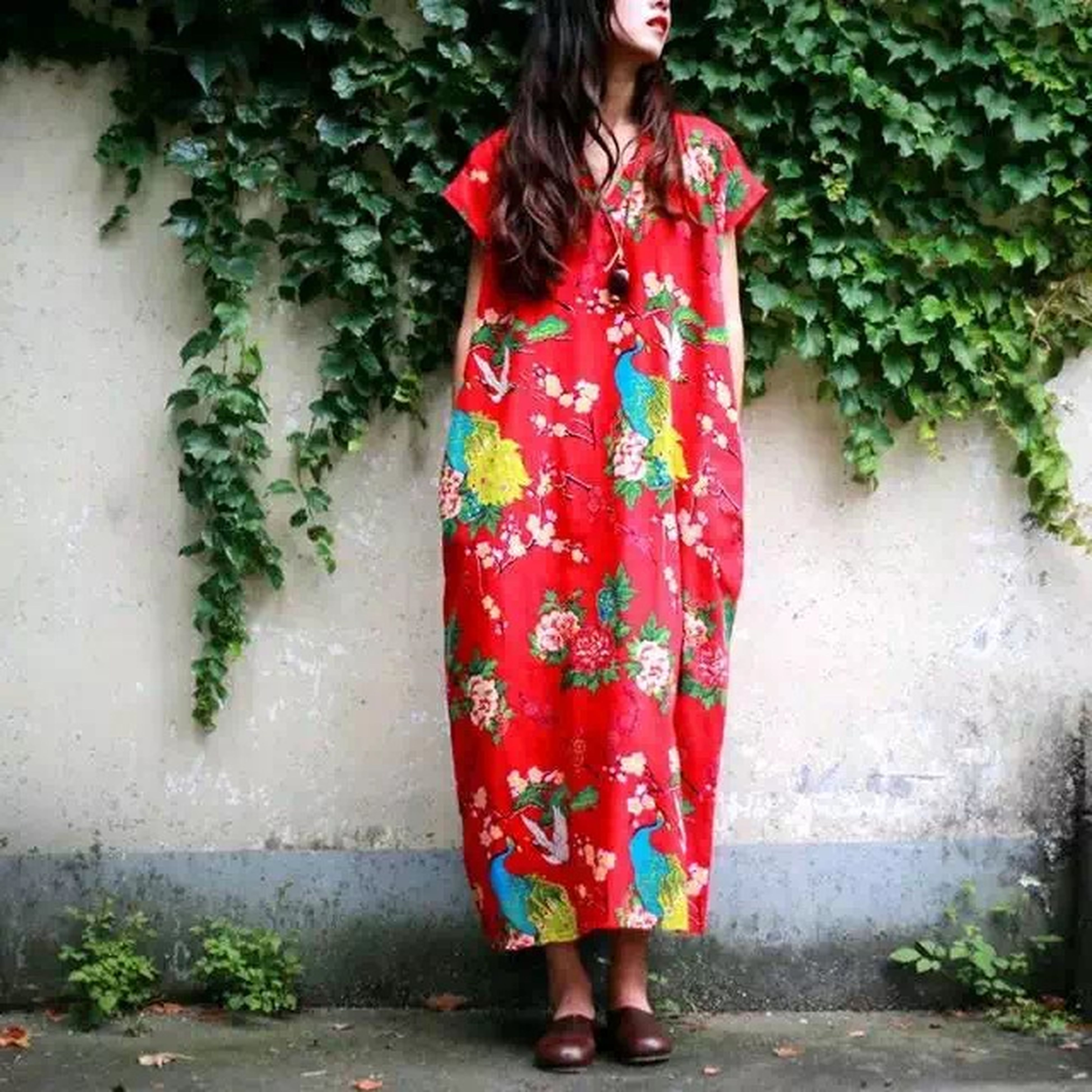 lifestyles, standing, casual clothing, wall - building feature, leisure activity, front view, red, full length, young adult, young women, person, built structure, wall, architecture, dress, three quarter length, plant