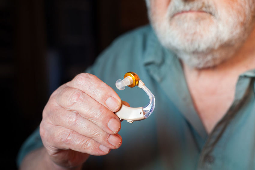 man holding hearing aid Audiology Close-up Communication Deaf Deafness Device Disabled Ear Equipment Gray Hair Hand Health Healthcare Healthcare And Medicine Hearing Aid Help Holding Illness Listen Medical Care Plastic Senior Men Sound Technology Wellbeing