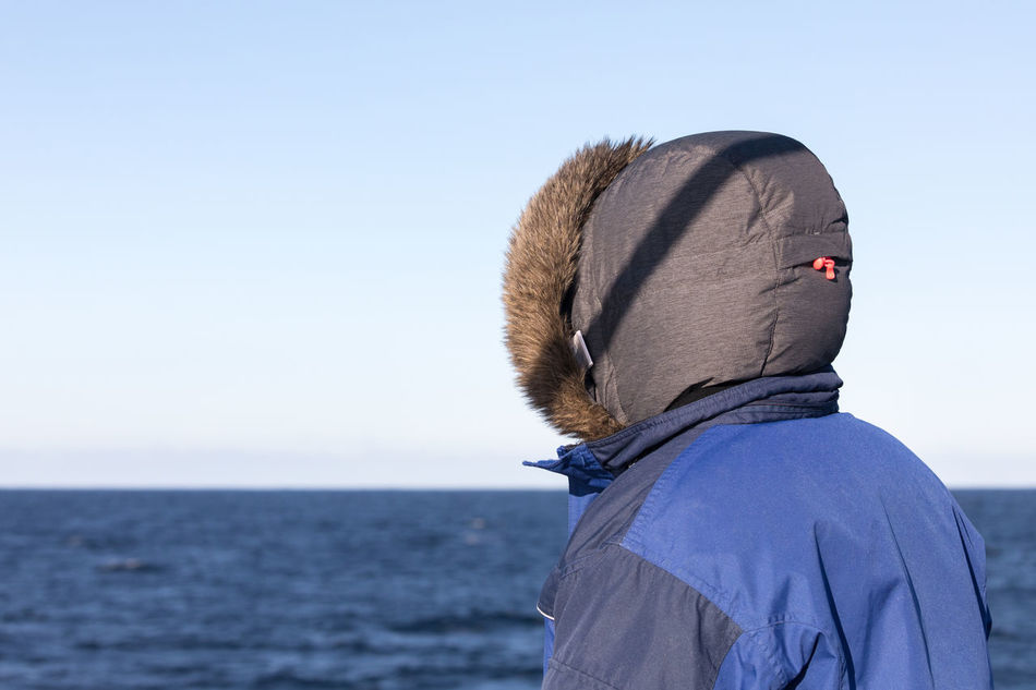 Woman in very warm clothes standing on a boat looking to the horizon Adult Beauty In Nature Blue Clear Sky Cold Temperature Distant Focus On Foreground Fur Hood - Clothing Horizon Horizon Over Water Looking At View Looking Away Nature Nordland County Norwegian Sea One Woman Only Polar Climate Rear View Remote Sea Sunny Warm Clothing Watching Winter