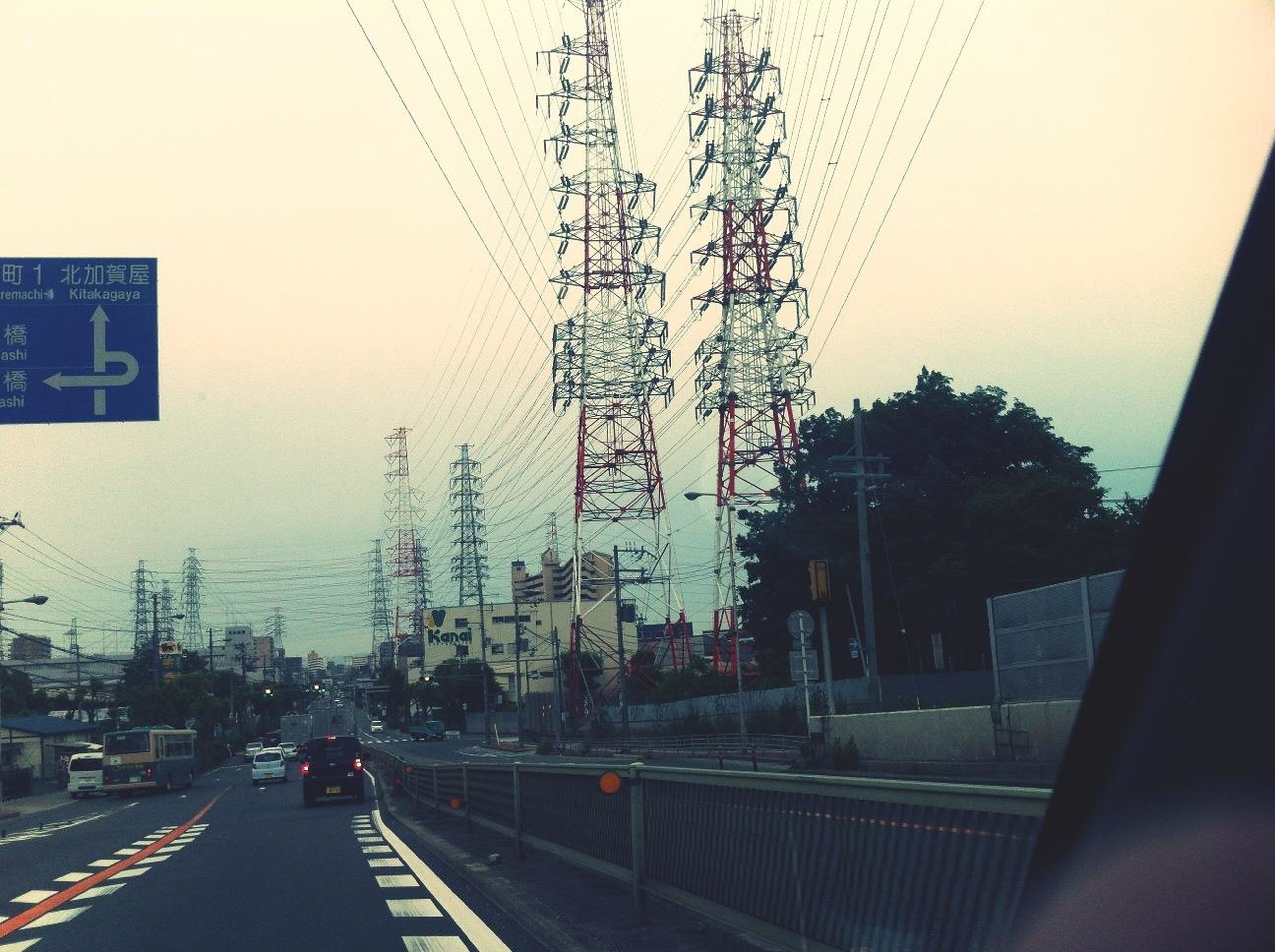 power line, transportation, electricity pylon, building exterior, road, cable, street, architecture, built structure, car, city, power supply, electricity, clear sky, sky, connection, power cable, land vehicle, mode of transport, tree
