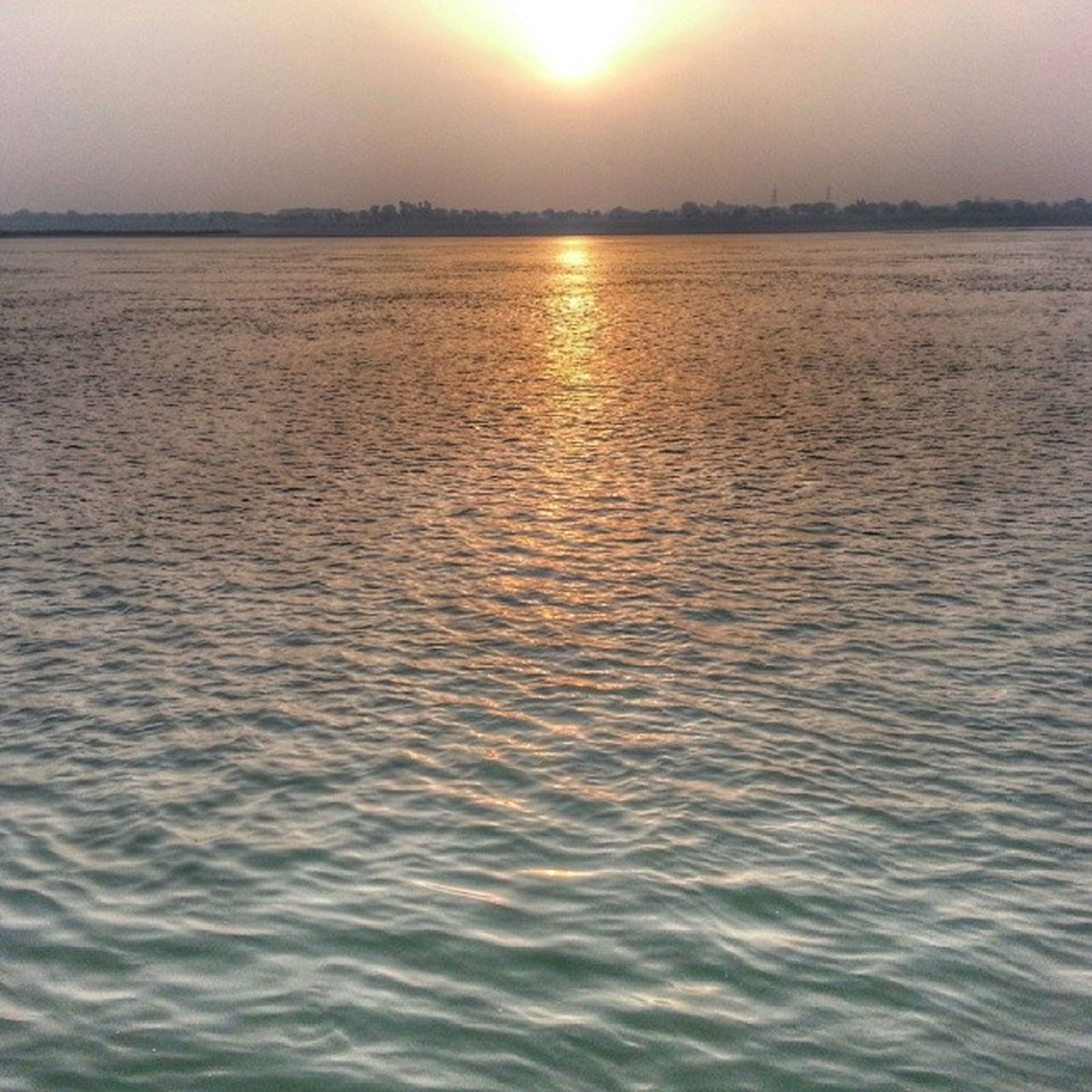 water, sunset, tranquil scene, sun, tranquility, scenics, beauty in nature, waterfront, reflection, rippled, nature, lake, idyllic, sunlight, sky, outdoors, no people, sea, river, non-urban scene