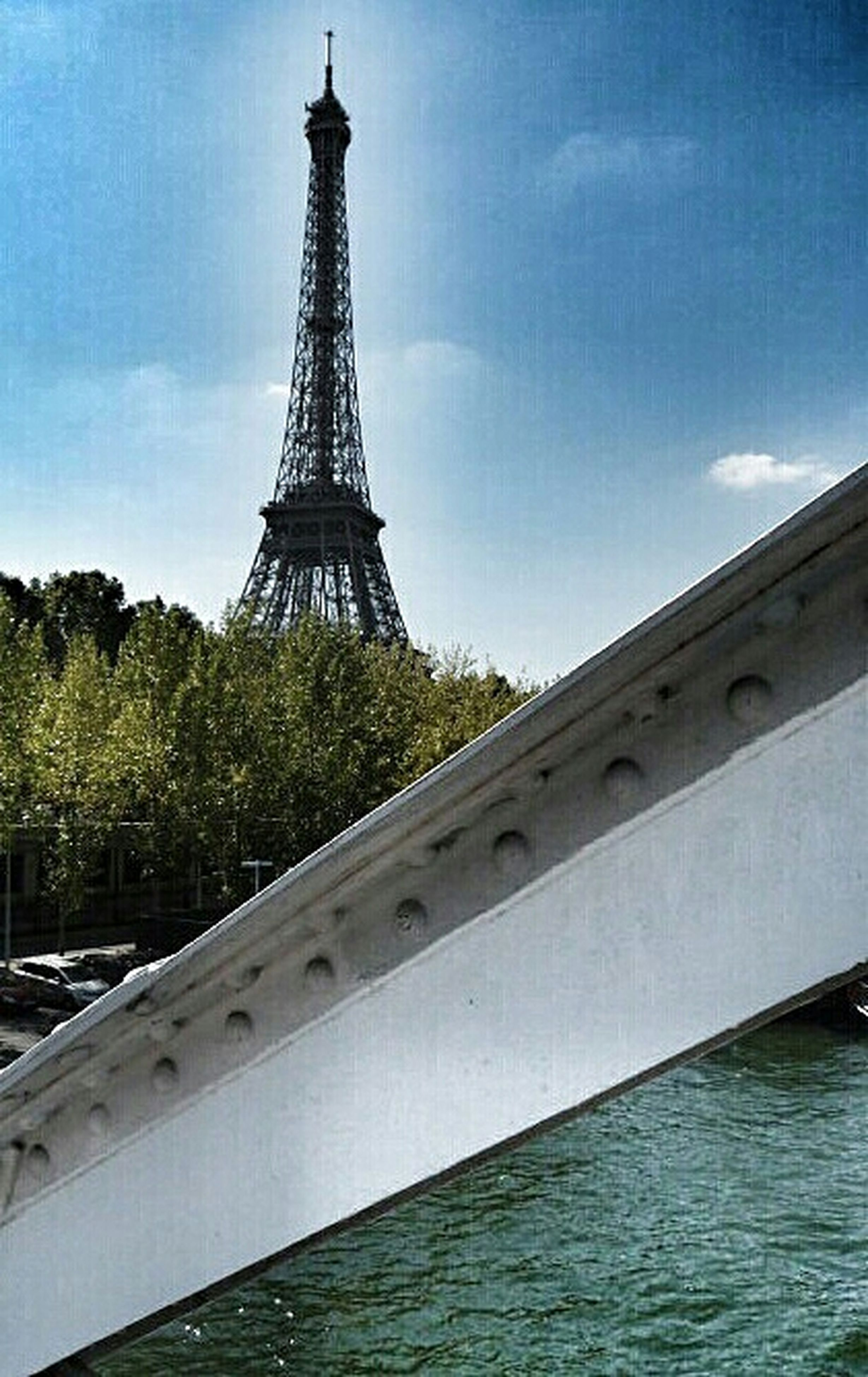 built structure, architecture, eiffel tower, tower, low angle view, international landmark, famous place, tall - high, travel destinations, sky, culture, capital cities, building exterior, travel, tourism, history, water, tree, metal, river