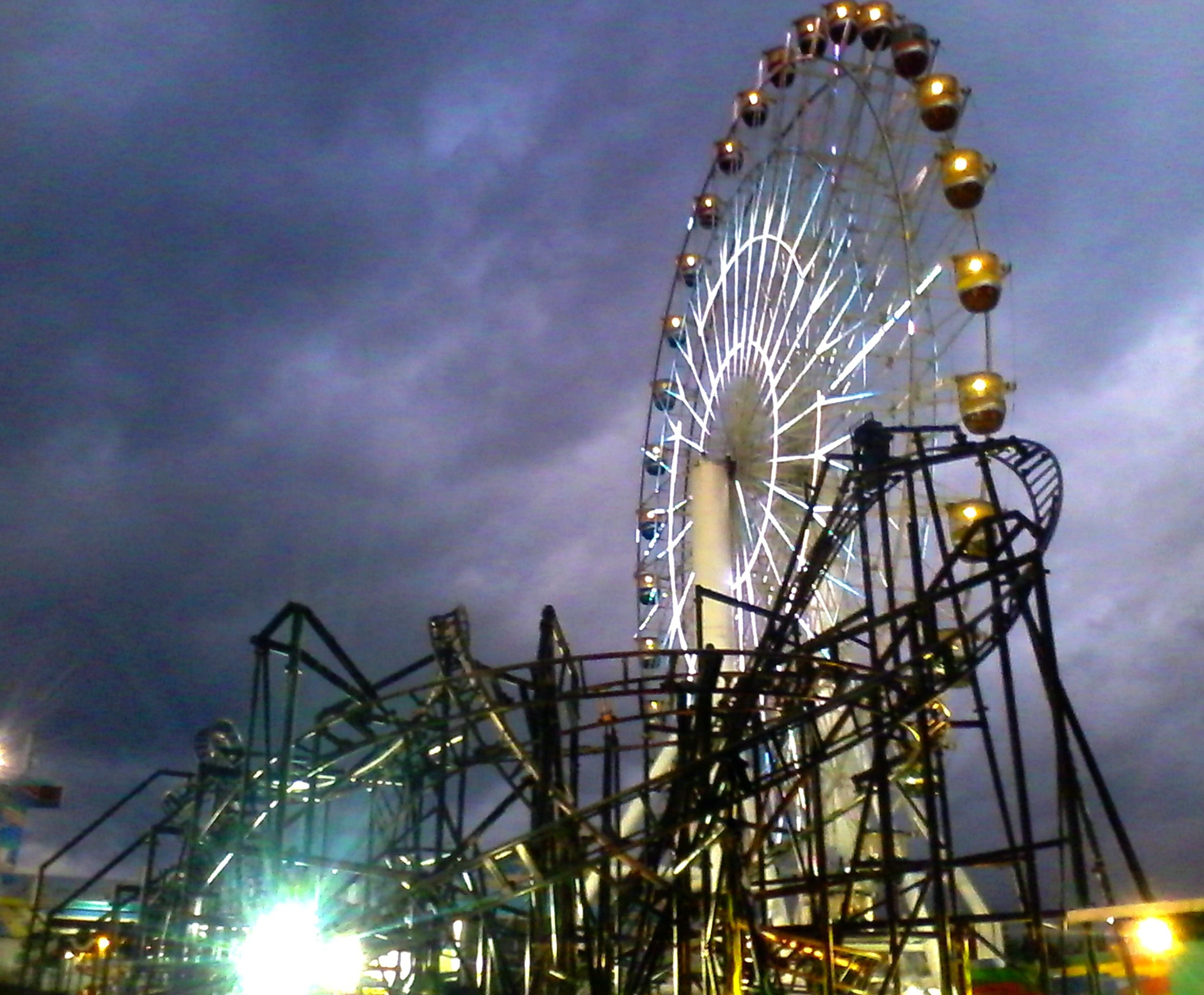 amusement park, ferris wheel, amusement park ride, low angle view, arts culture and entertainment, sky, cloud - sky, illuminated, built structure, silhouette, night, dusk, outdoors, metal, fun, cloudy, no people, big wheel, tall - high, fairground ride