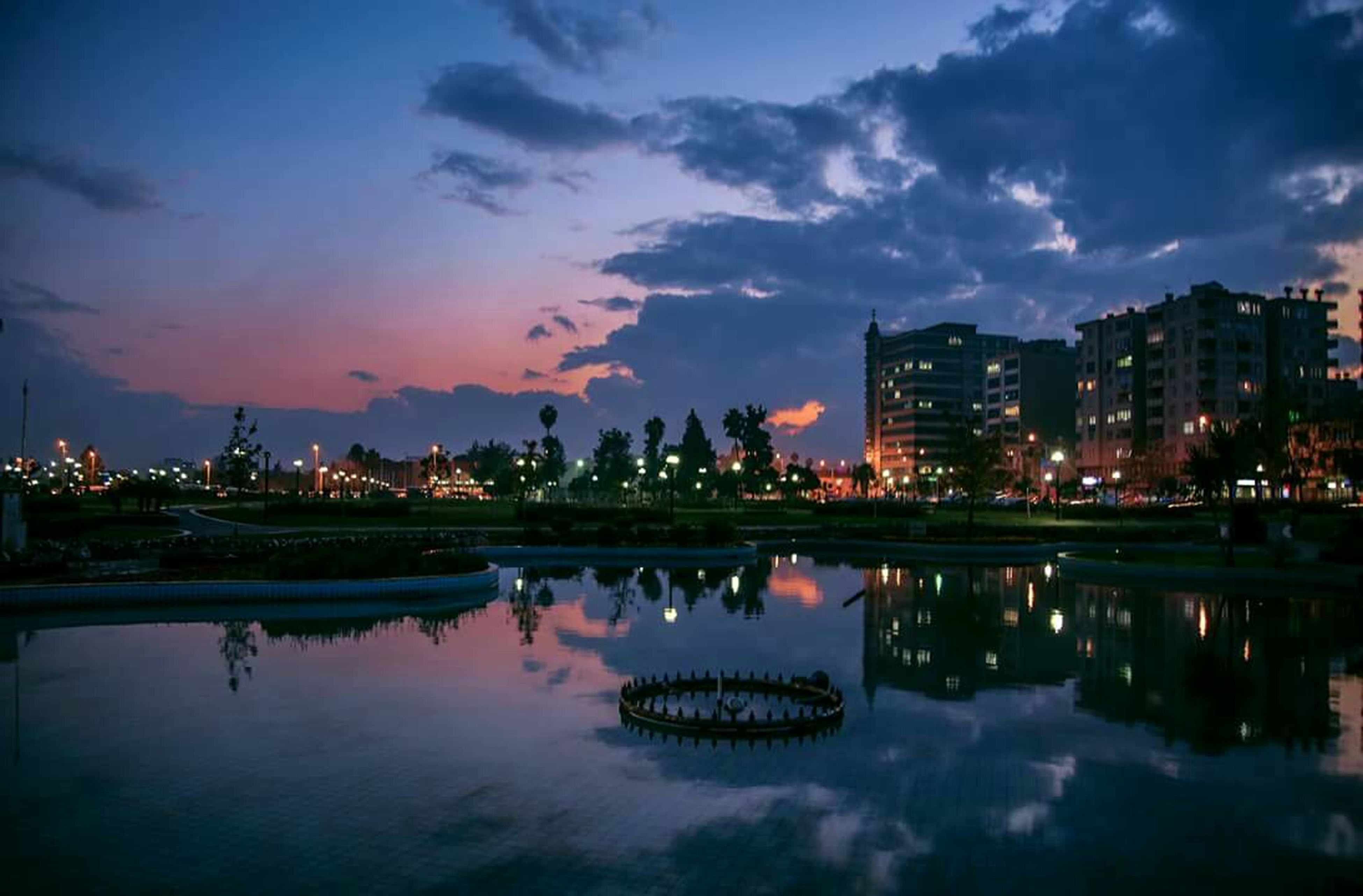 reflection, water, sky, illuminated, waterfront, building exterior, lake, built structure, architecture, dusk, cloud - sky, night, river, silhouette, city, sunset, tranquility, standing water, cloud, scenics