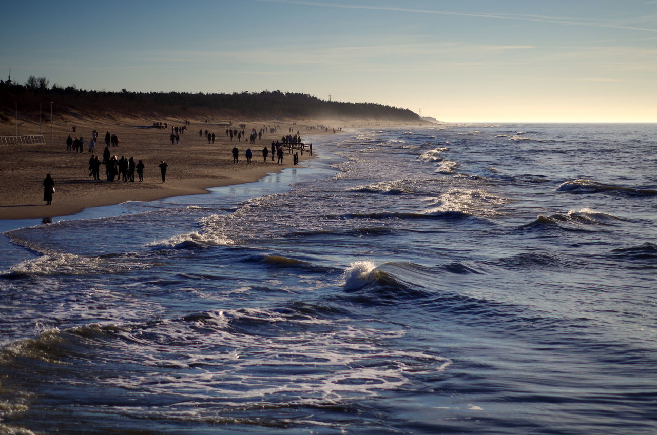 nature, sea, beauty in nature, water, scenics, sky, sunset, wave, real people, large group of people, leisure activity, outdoors, beach, tranquil scene, vacations, waterfront, tranquility, travel destinations, sunlight, day, animals in the wild, horizon over water, men, swimming, bird, mammal, people