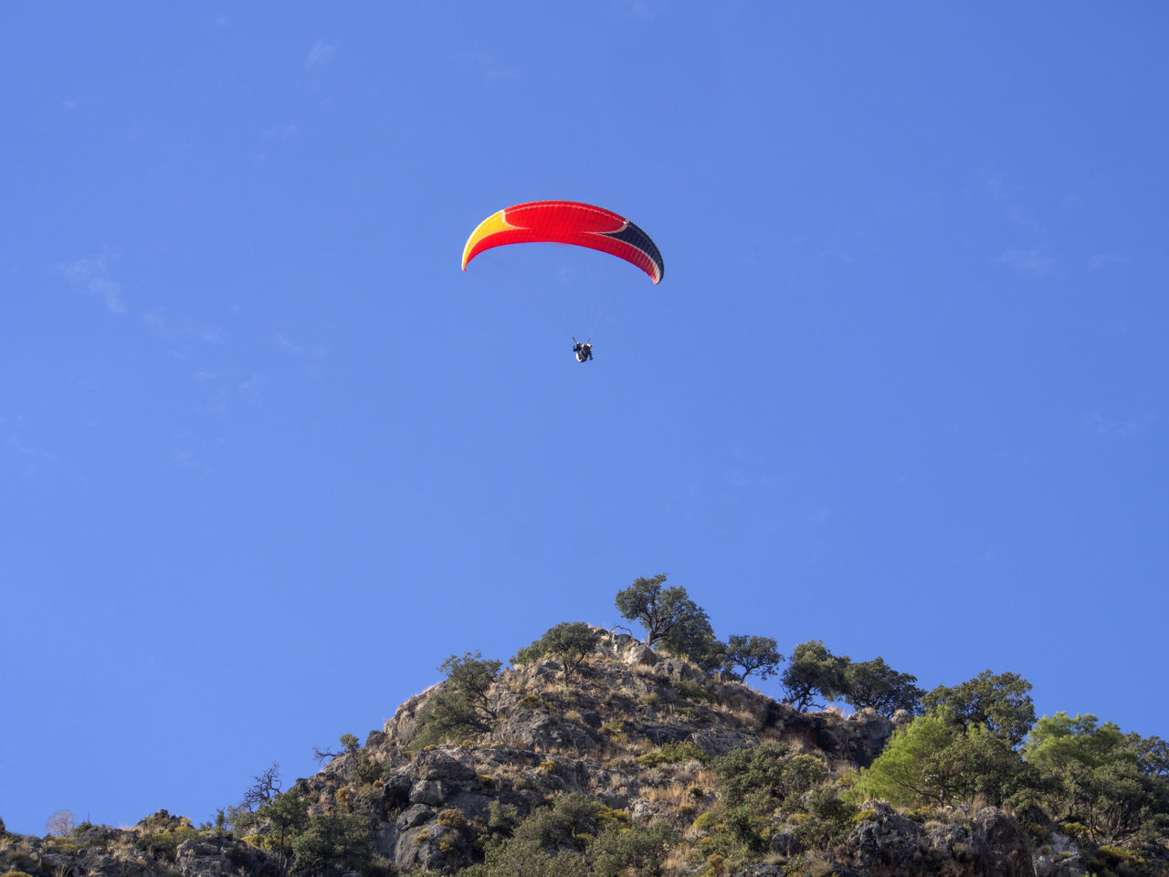 Low Angle View Of Person Paragliding Over Mountain Against Blue Sky